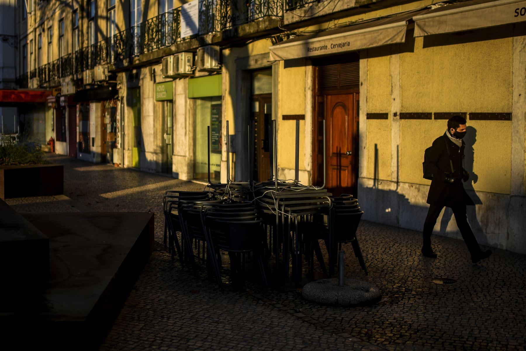 Un hombre pasa frente a un restaurante cerrado en Lisboa,  Portugal entró en un nuevo bloqueo por un aumento en los casos de coronavirus. El nuevo coronavirus ha matado al menos a 1.994.833 personas. Foto: AFP