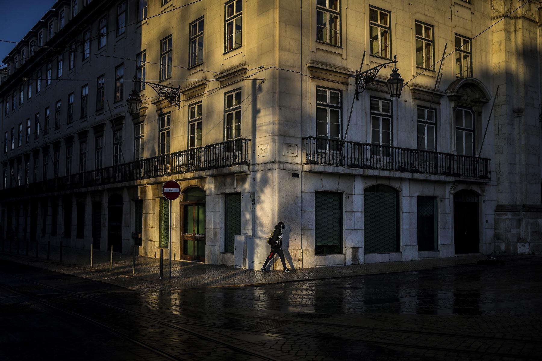 Un hombre camina por las calles vacías de Lisboa, Portugal entró en un nuevo bloqueo por un aumento en los casos de coronavirus. El nuevo coronavirus ha matado al menos a 1,994,833 personas. Foto: AFP