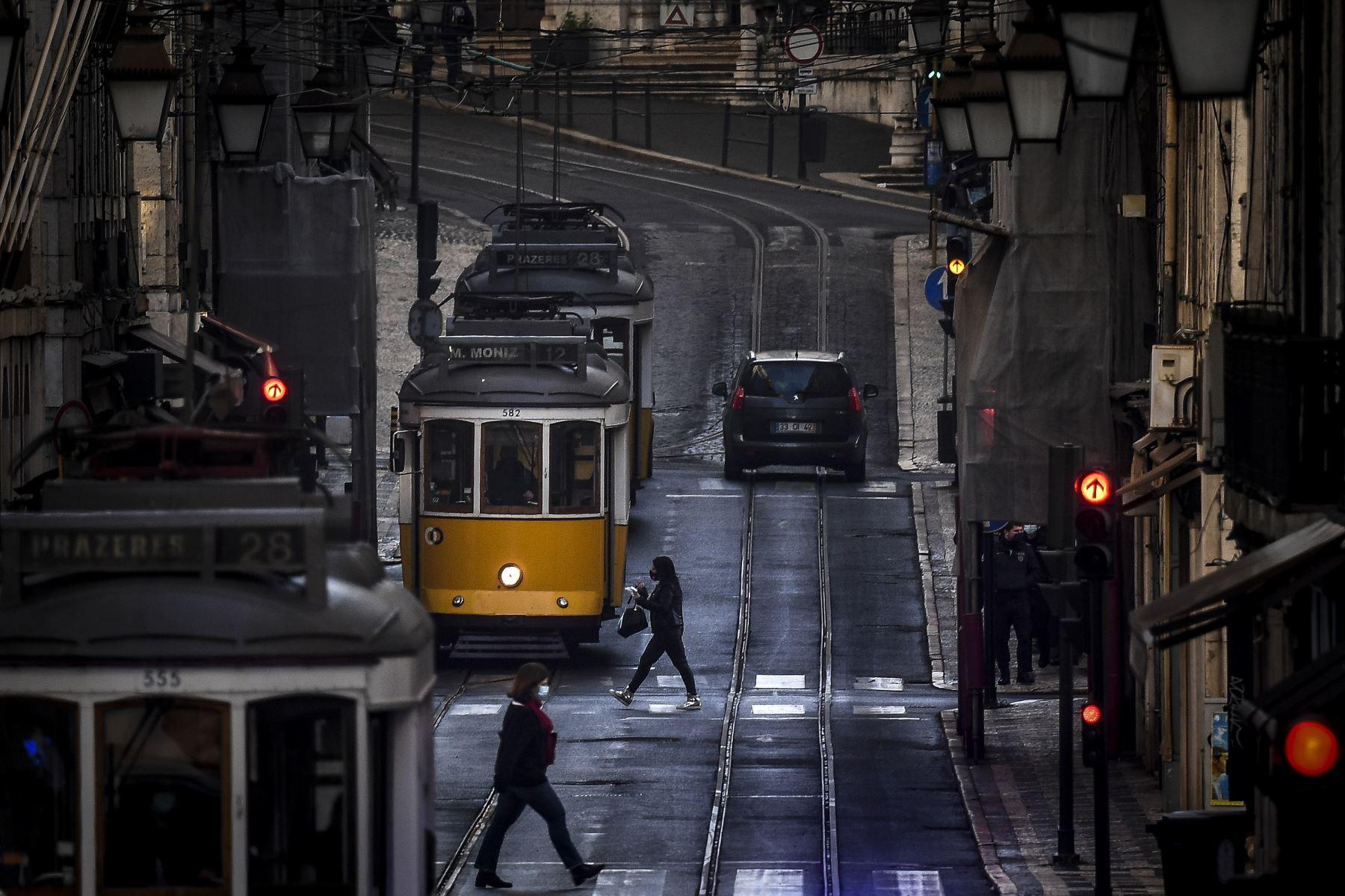 La gente pasa frente a los tranvías en Lisboa, Portugal entró en un nuevo bloqueo por un aumento en los casos de coronavirus. El nuevo coronavirus ha matado al menos a 1.994.833 personas.Foto: AFP