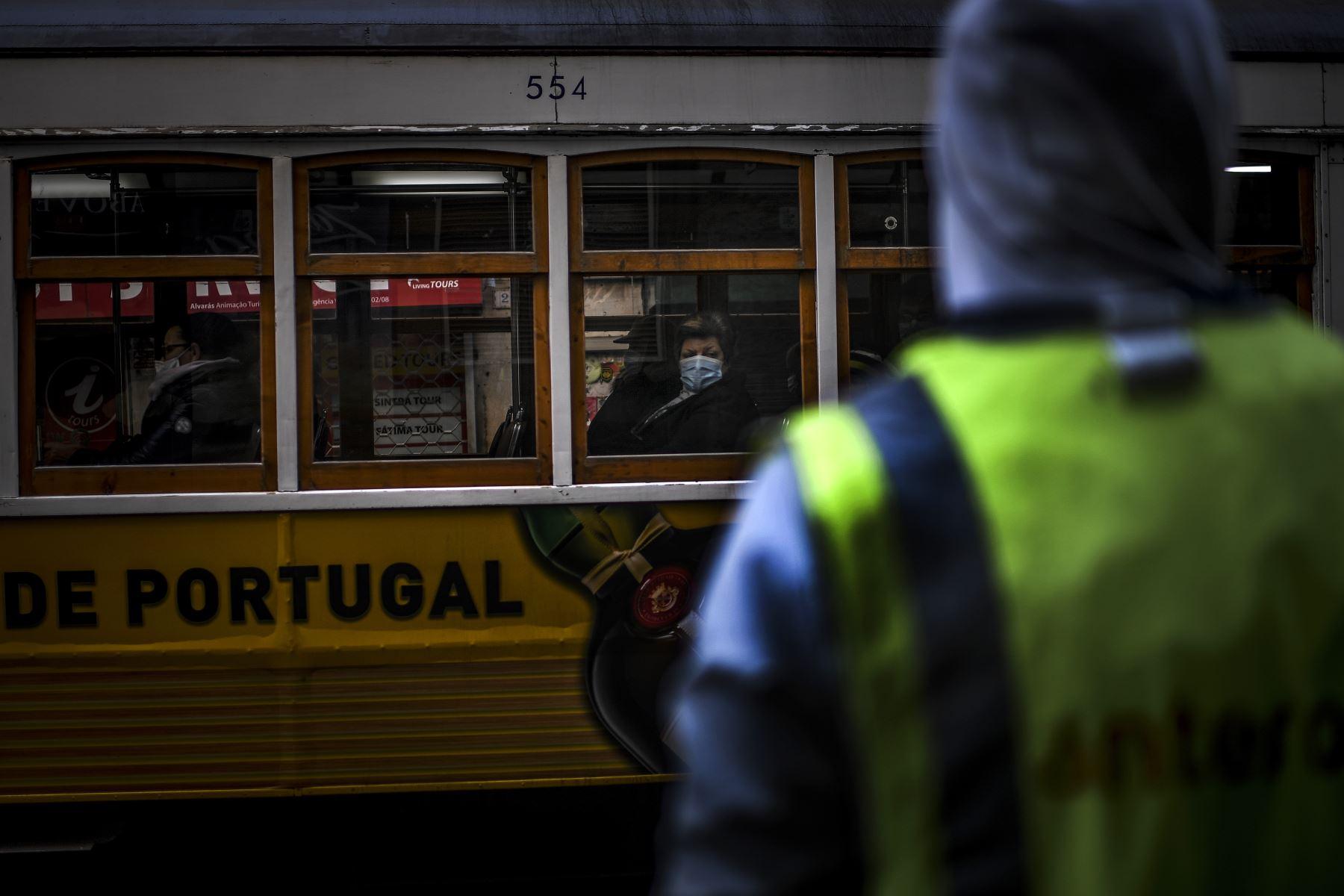 Una mujer con una máscara facial viaja en un tranvía en Lisboa, Portugal entró en un nuevo bloqueo por un aumento en los casos de coronavirus. El nuevo coronavirus ha matado al menos a 1.994.833 personas. Foto: AFP