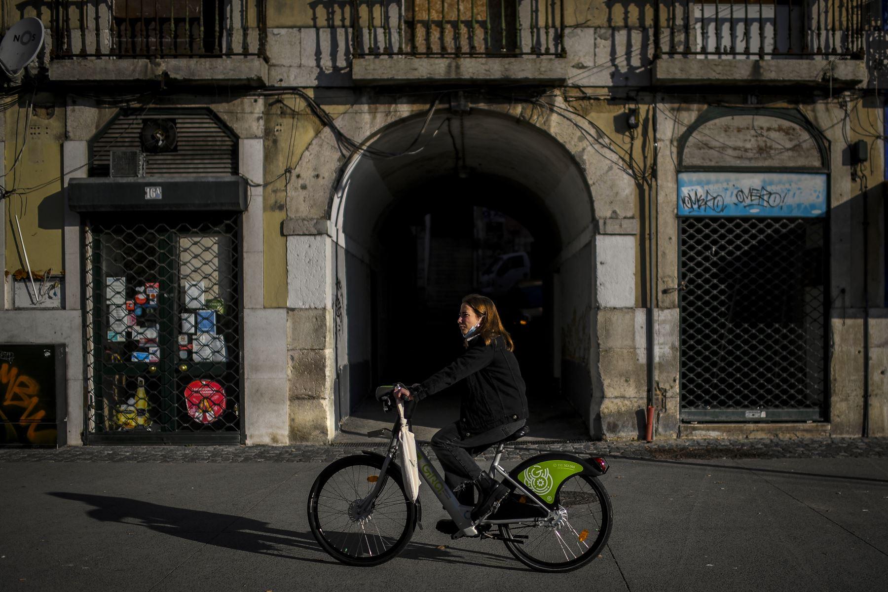 Una mujer pasa en bicicleta frente a tiendas cerradas en Lisboa Portugal, que  entró en un nuevo bloqueo por un aumento en los casos de coronavirus.  Foto: AFP
