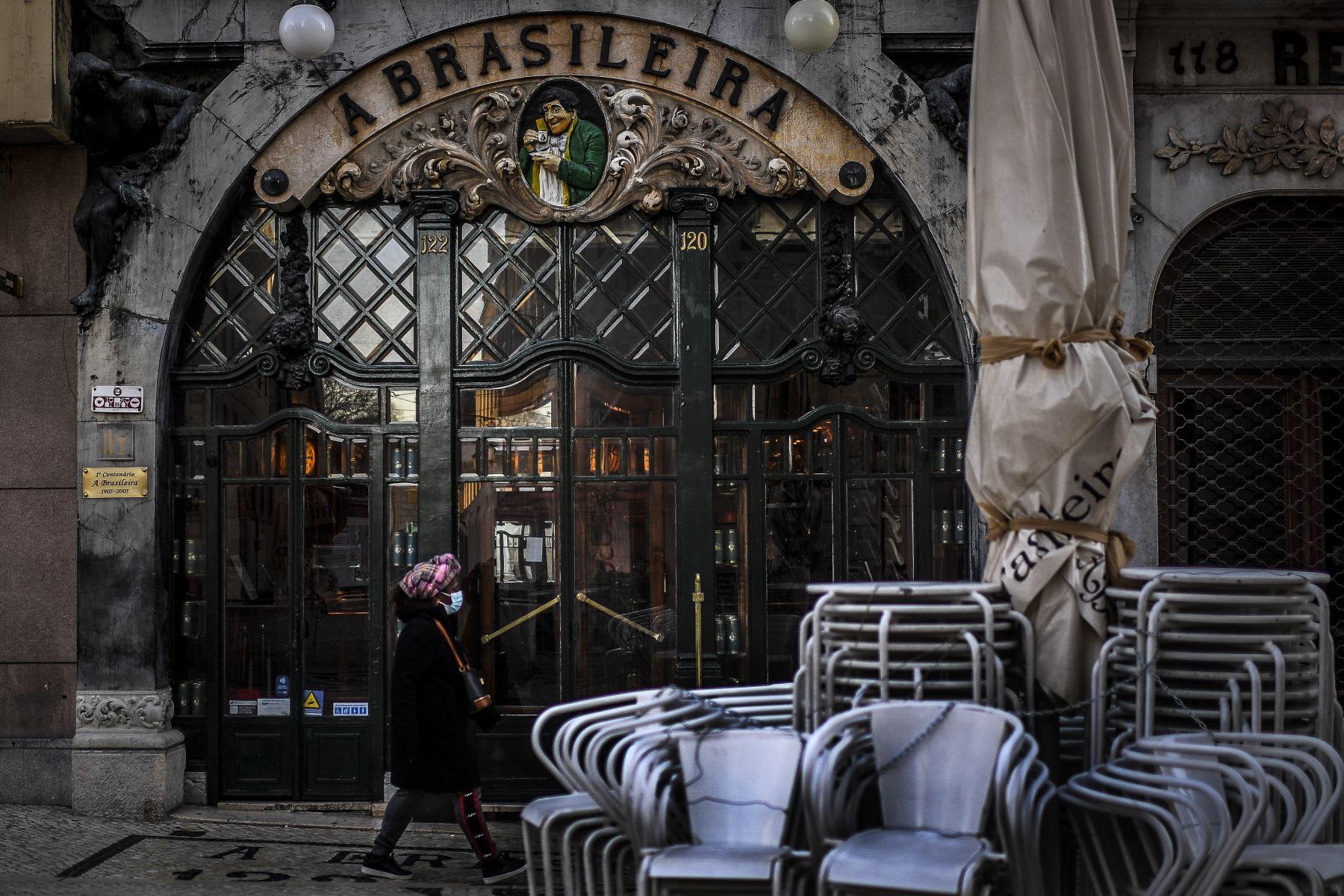 """Una mujer pasa frente a la cafetería """"A Brasileira"""" en Lisboa Portugal, que  ingresó a un nuevo bloqueo por un aumento en los casos de coronavirus. El nuevo coronavirus ha matado al menos a 1.994.833 personas. Foto: AFP"""