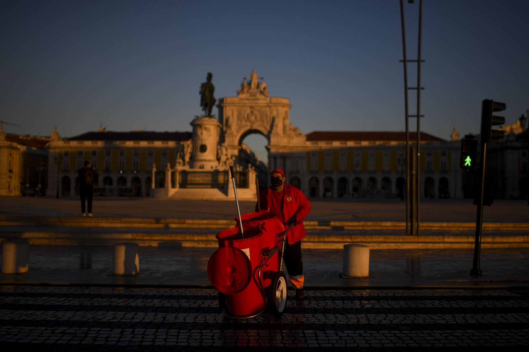 Un trabajador de la ciudad trabaja en la plaza Comercio en Lisboa Portugal, que entró en un nuevo bloqueo por un aumento en los casos de coronavirus. El nuevo coronavirus ha matado al menos a 1.994.833 personas. Foto: AFP
