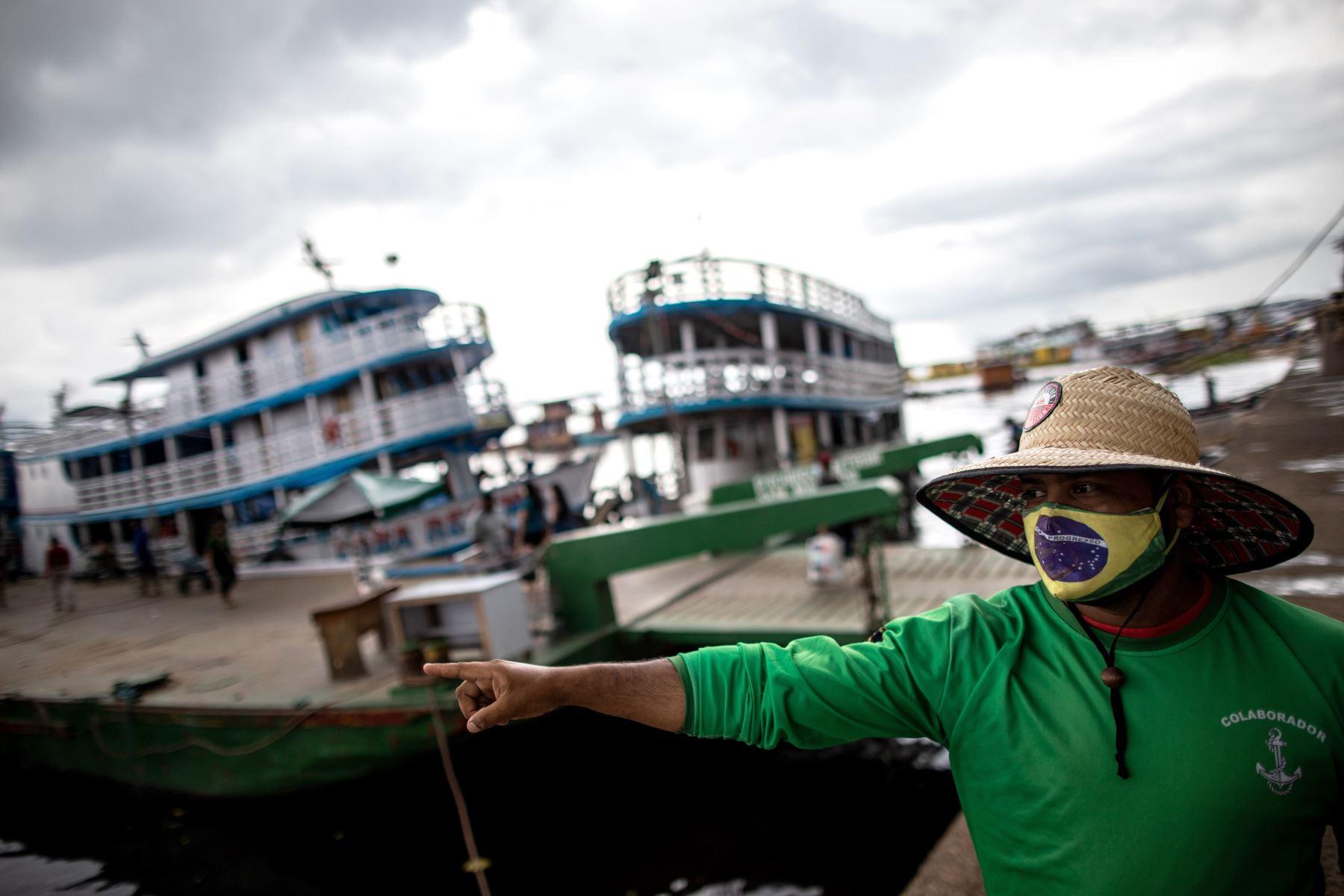 Un hombre con tapabocas de diseño de la bandera brasileña señala hacia el río Amazonas hoy, en Manaos, Brasil. La nueva variante de la covid detectada en la Amazonía brasileña  no solo llevó a que Reino Unido vetara los vuelos desde Portugal y Suramérica sino también a algunas regiones de Brasil. Foto: EFE