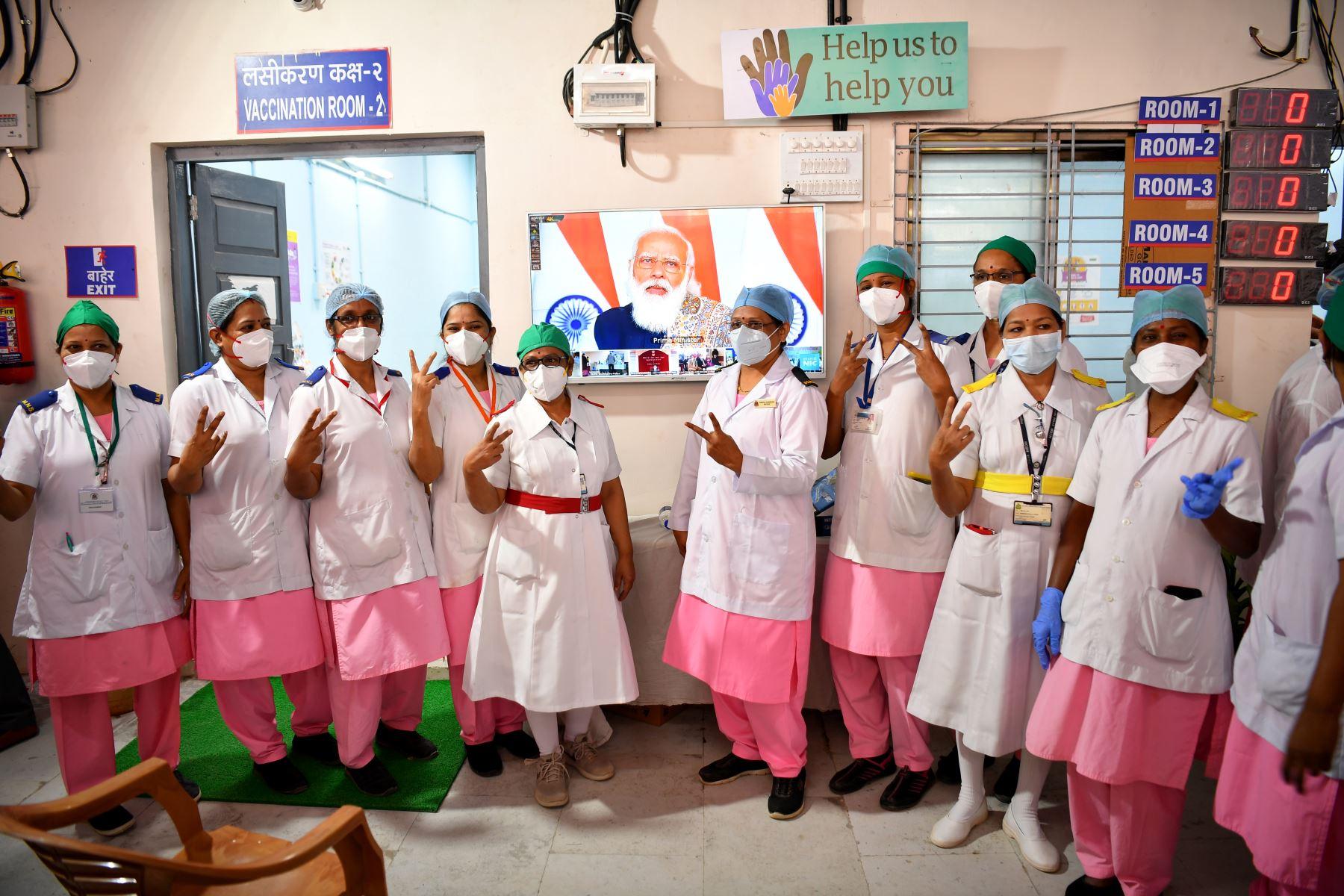 Las enfermeras del Hospital Rajawadi hacen el gesto del signo de la victoria mientras posan frente a un televisión transmitiendo un discurso en vivo del primer ministro de la India, Narendra Modi, antes del inicio de la campaña de vacunación contra el coronavirus Covid-19 en Mumbai. Foto: AFP