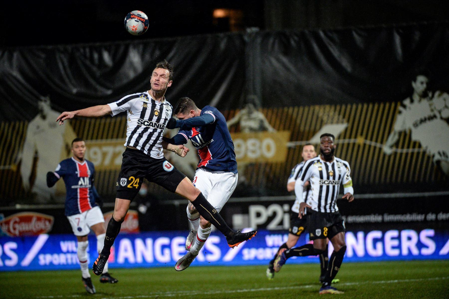Defensor francés del Angers, Romain Thomas, salta por el balón con el centrocampista español del PSG, Pablo Sarabia, durante el partido de fútbol francés L1 entre Angers y PSG en el Estadio Raymond Kopa en Angers, oeste de Francia. Foto: AFP