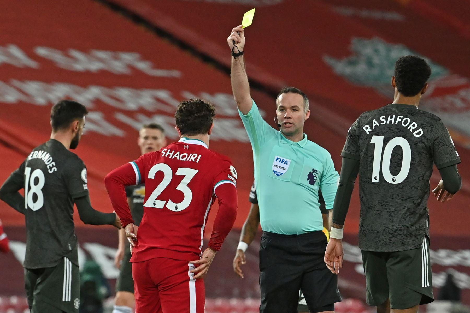 El árbitro inglés Paul Tierney muestra una tarjeta amarilla al centrocampista suizo del Liverpool Xherdan Shaqiri durante el partido de fútbol de la Premier League inglesa entre Liverpool y Manchester United en Anfield en Liverpool. Foto: AFP