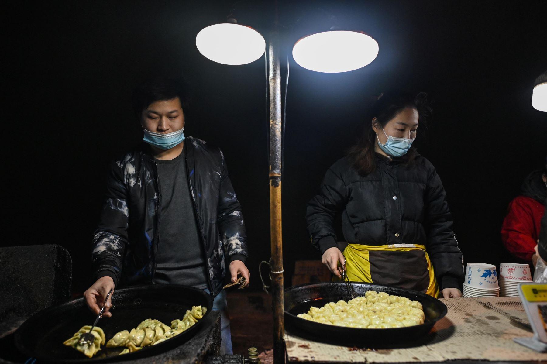 Una pareja que usa mascarilla como medida preventiva contra el covid-19, prepara comida para vender en una calle de Wuhan provincia de Hubei; en el centro de China. Foto: AFP