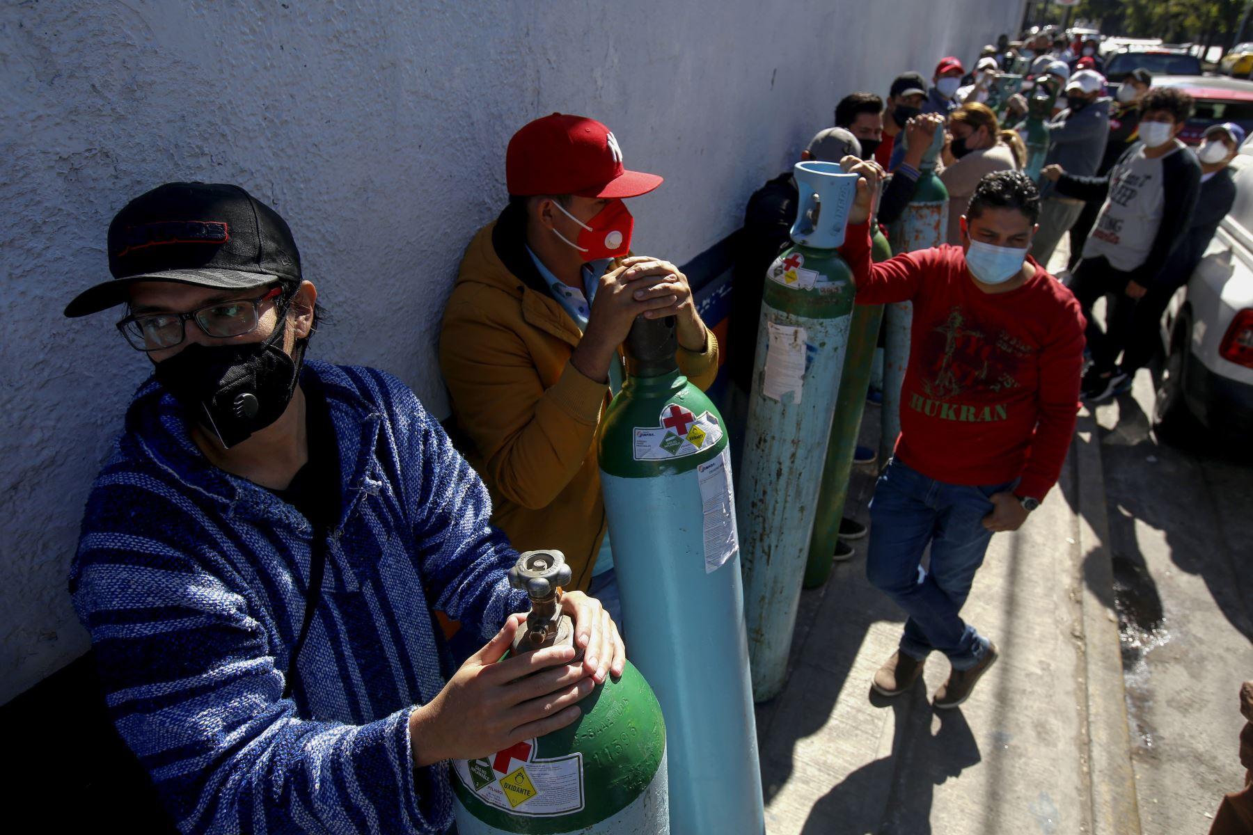 Personas hacen cola para recargar los tanques de oxígeno de sus familiares infectados con covid-19, debido a la escasez de gas medicinal, en Guadalajara Estado de México.  Foto: AFP