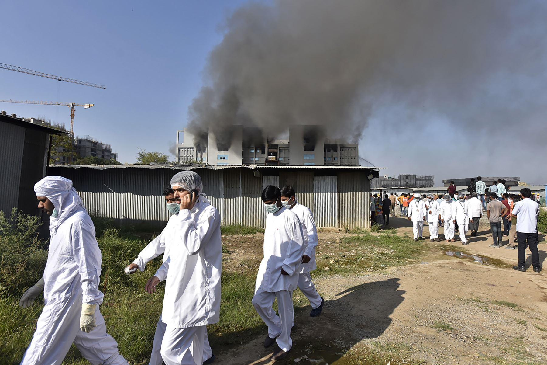 Los trabajadores con equipo de protección caminan después de que estalló un incendio en el Serum Institute de India en  el mayor fabricante de vacunas del mundo. Foto: AFP
