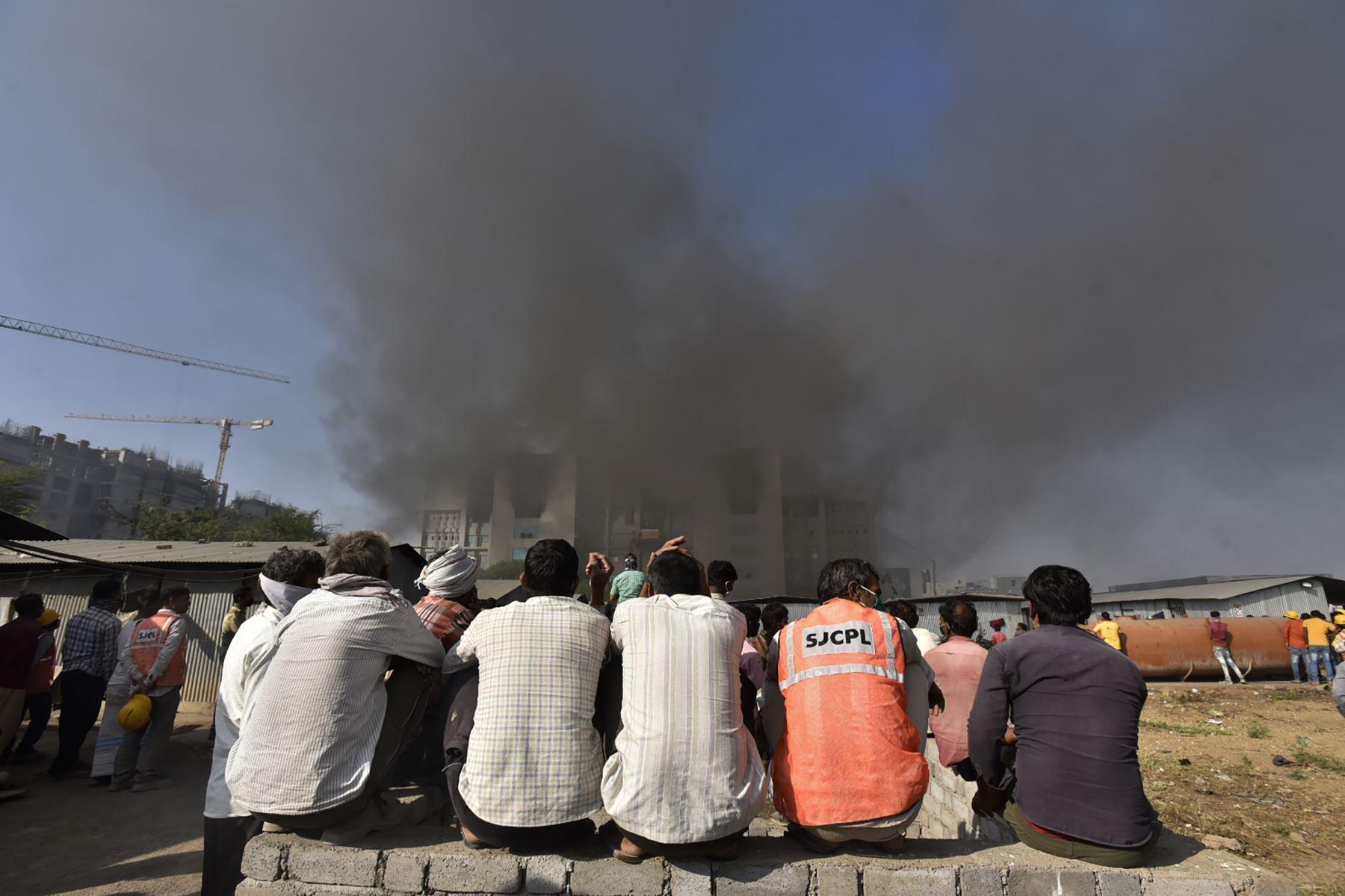 La gente observa cómo se eleva el humo después de que estalló un incendio  en el Serum Institute de India, el mayor fabricante mundial de vacunas, los medios dijeron que la producción de la vacuna contra el coronavirus  no se vio afectada. AFP