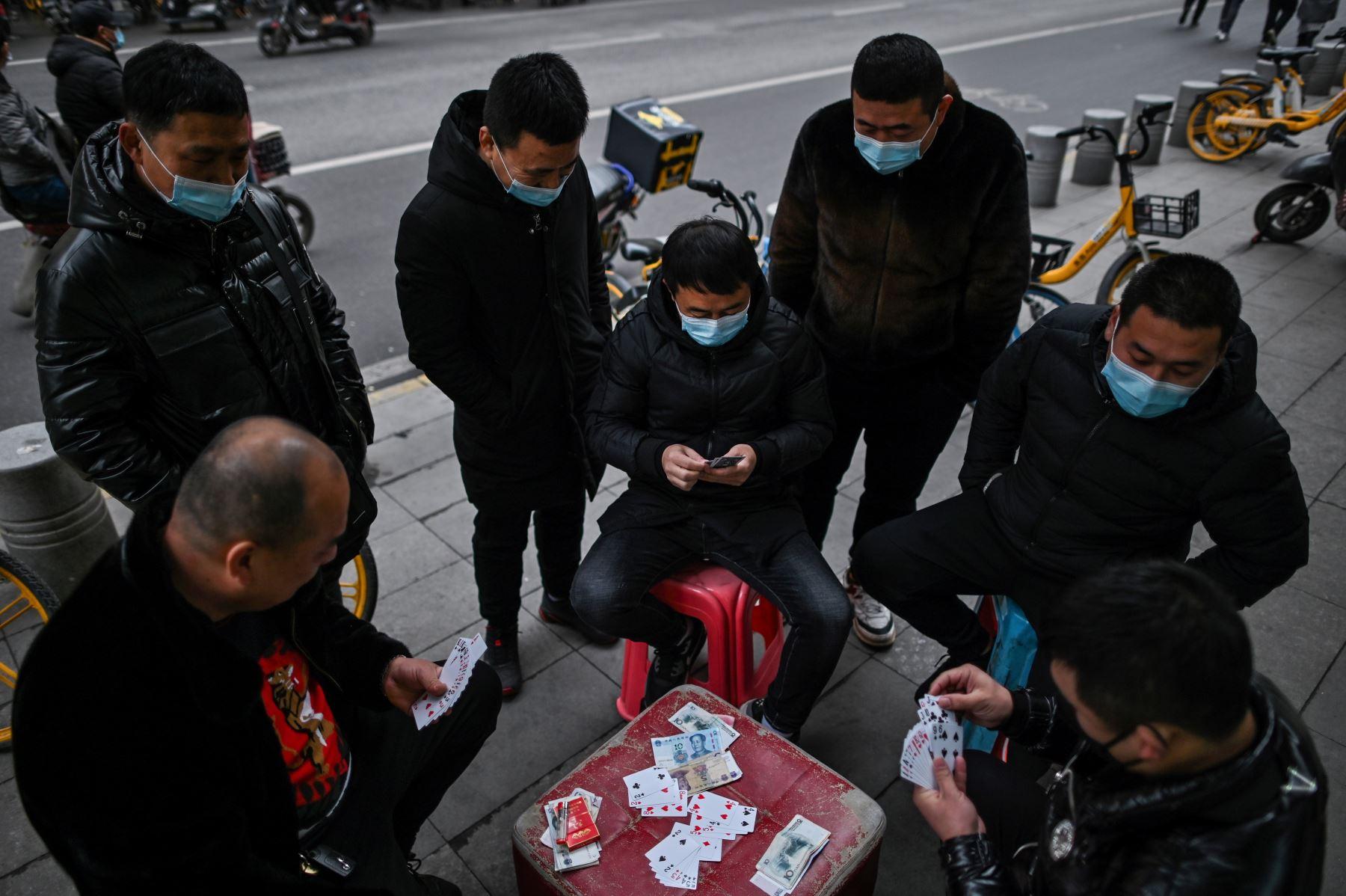 Hombres con mascarillas como medida preventiva contra el coronavirus Covid-19 juegan a las cartas en una calle de Wuhan. Foto: AFP