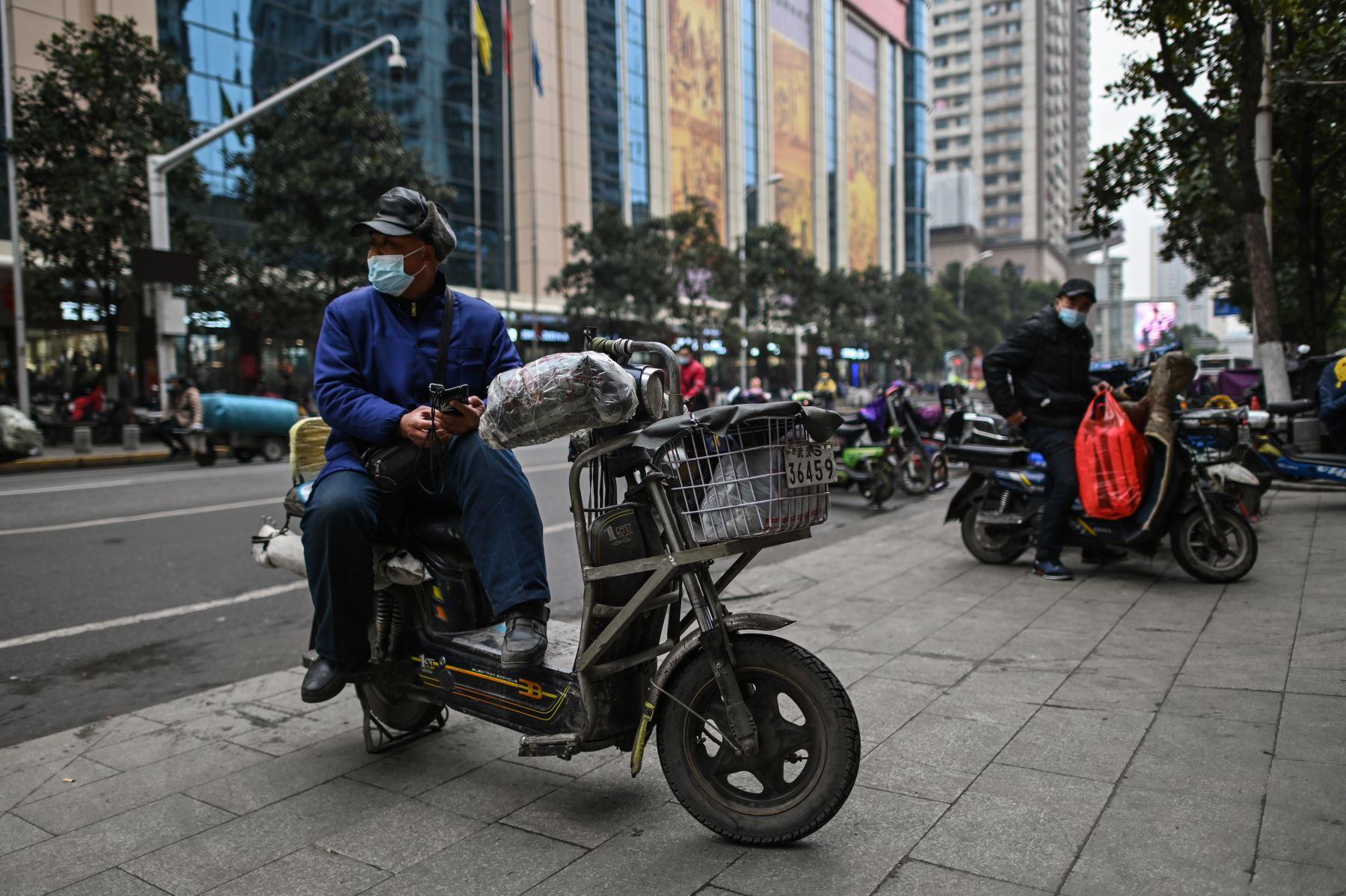 Un hombre que llevaba una mascarilla como medida preventiva contra el coronavirus Covid-19 descansa sobre su scooter en Wuhan. Foto: AFP
