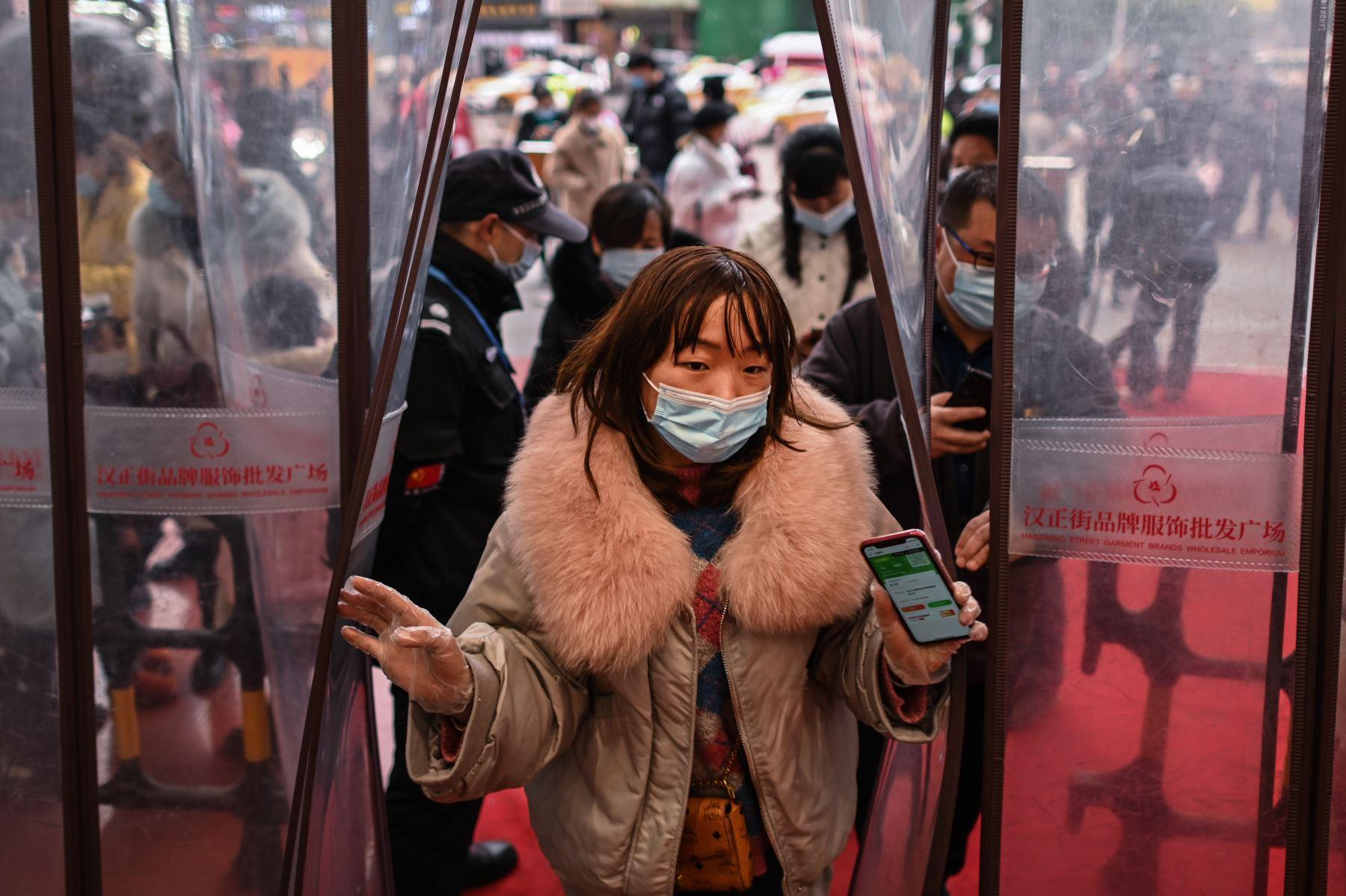 Una mujer que usa una mascarilla como medida preventiva contra el coronavirus Covid-19 ingresa a un centro comercial luego de mostrar su código de salud en Wuhan. Foto: AFP