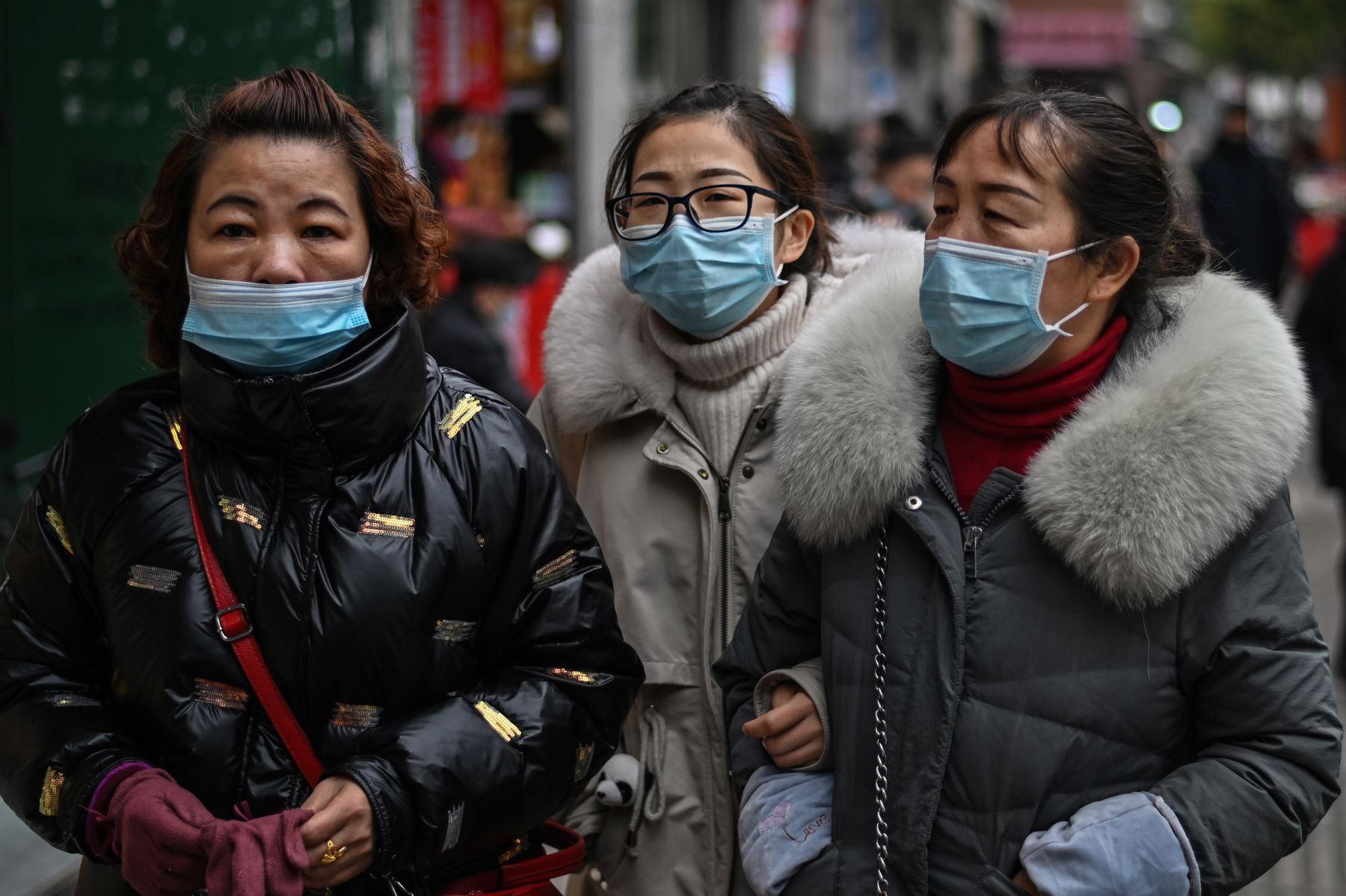 Los peatones con máscaras faciales como medida preventiva contra el coronavirus Covid-19 caminan en una calle de Wuhan. Foto: AFP