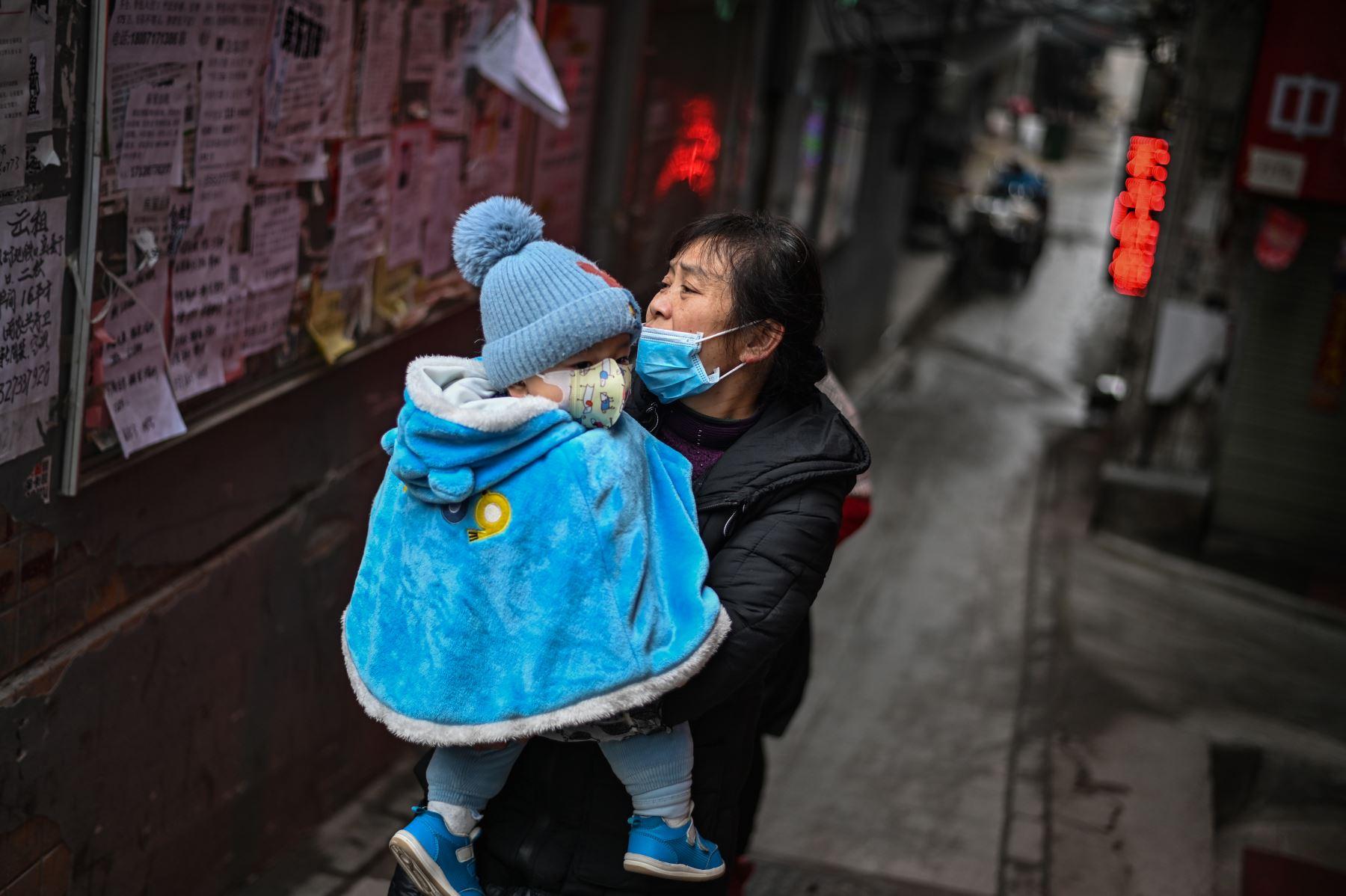 Una mujer que usa una mascarilla como medida preventiva contra el coronavirus Covid-19 camina por un camino con un bebé en brazos en Wuhan. Foto: AFP