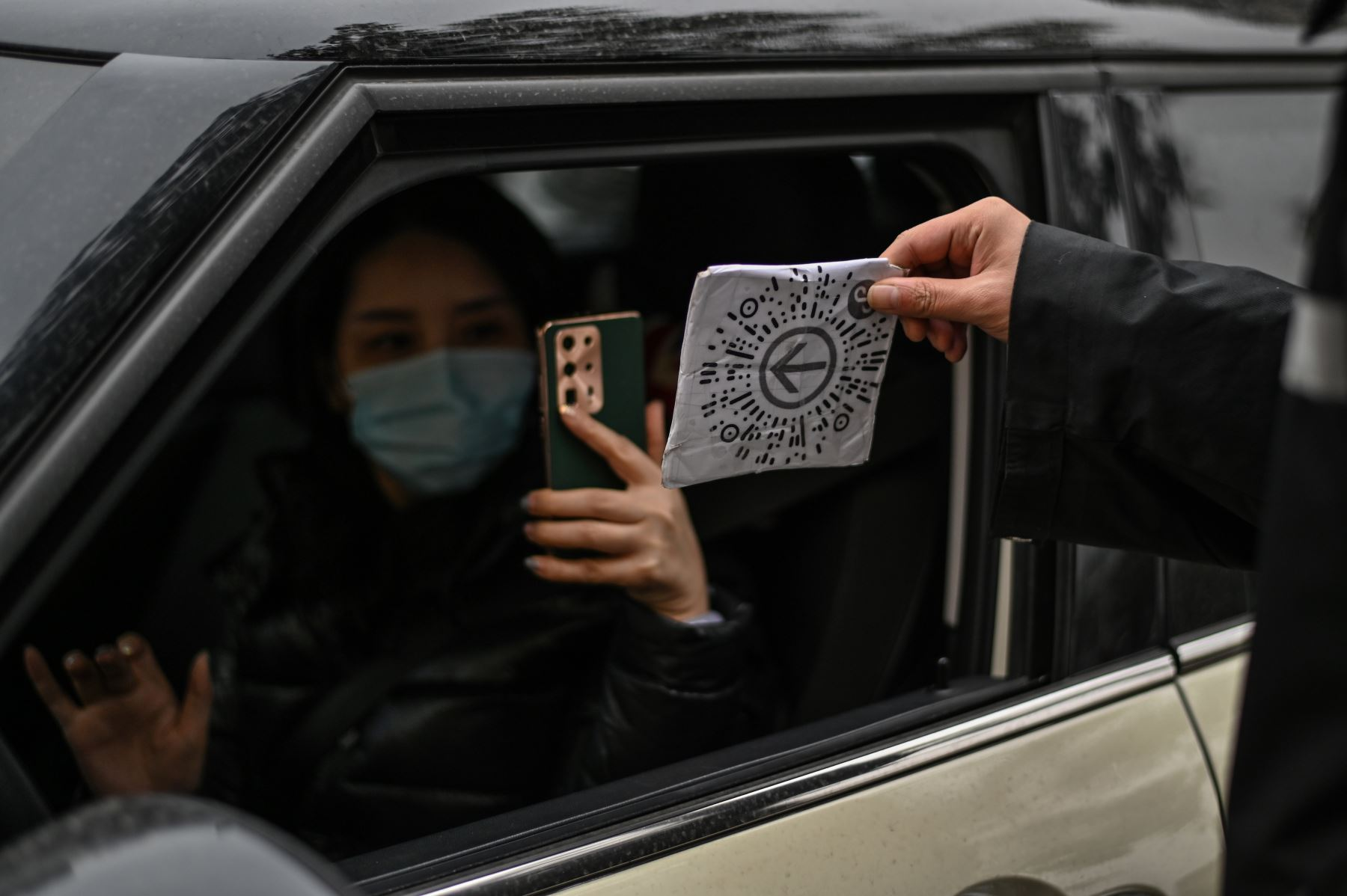Una mujer con mascarilla como medida preventiva contra el coronavirus Covid-19 escanea un código de salud para ingresar al área de estacionamiento de un centro comercial en Wuhan. Foto: AFP