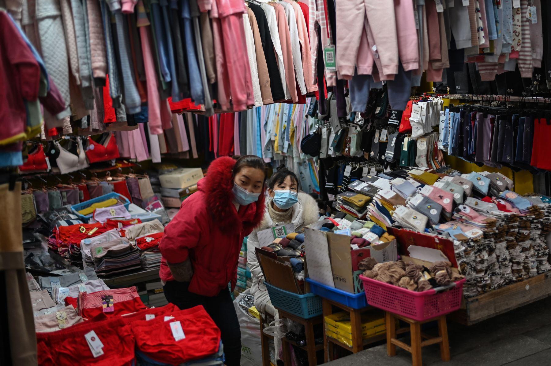 Los vendedores que usan máscaras faciales como medida preventiva contra el coronavirus Covid-19 esperan a los clientes en una tienda en Wuhan. Foto: AFP