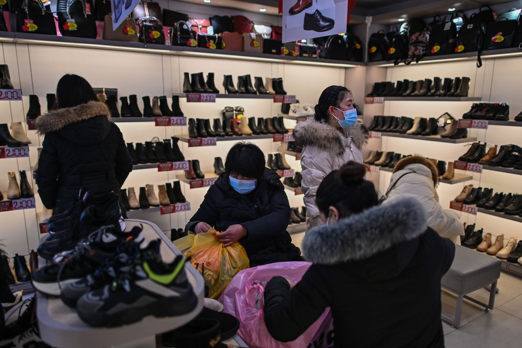 Personas que usan mascarillas como medida preventiva contra el coronavirus Covid-19 visitan una zapatería en Wuhan. Foto: AFP