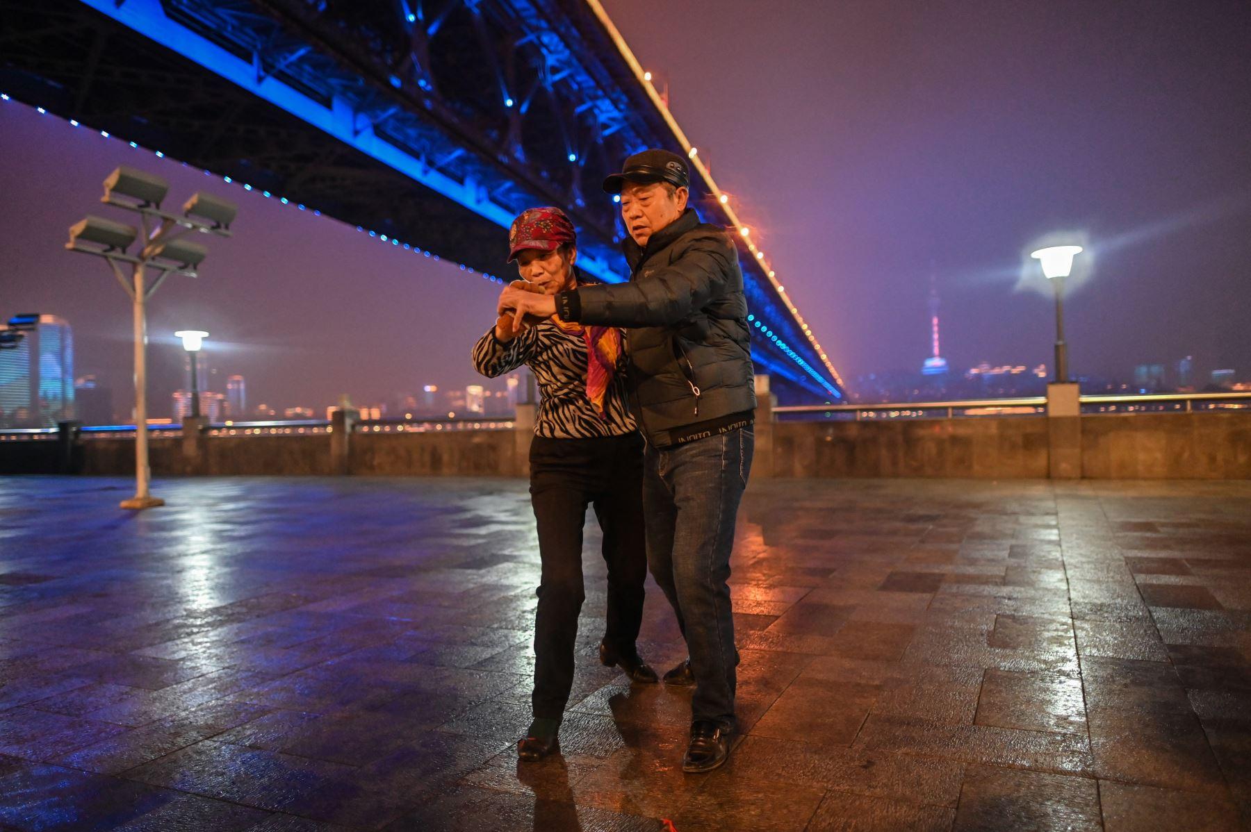 Una pareja baila junto al puente de Wuhan que cruza el río Yangtze en Wuhan, provincia de Hubei, en el centro de China. Foto: AFP