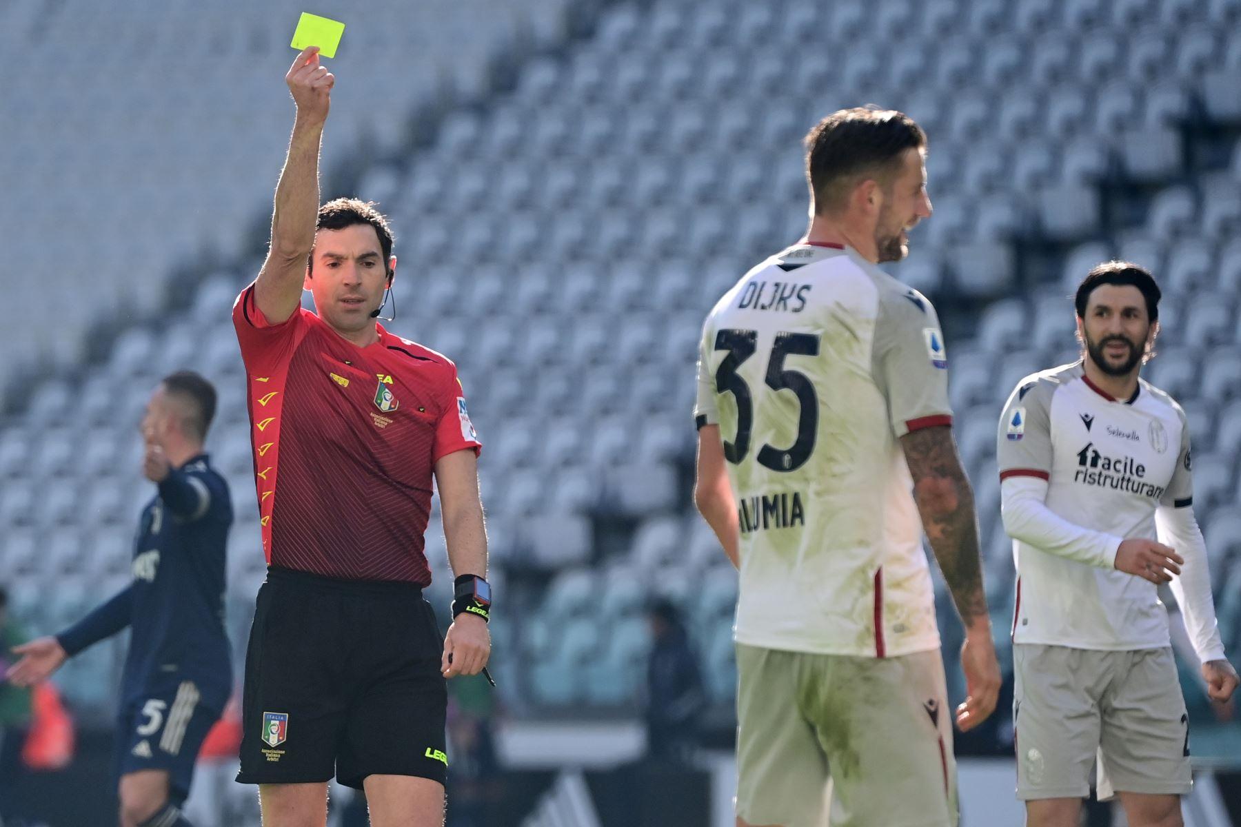 El árbitro italiano Juan Luca Sacchi da una tarjeta amarilla al defensor holandés de Bolonia Mitchell Dijks durante el partido de fútbol de la Serie A italiana Juventus vs Bolonia  en el estadio de la Juventus de Turín.  Foto: AFP