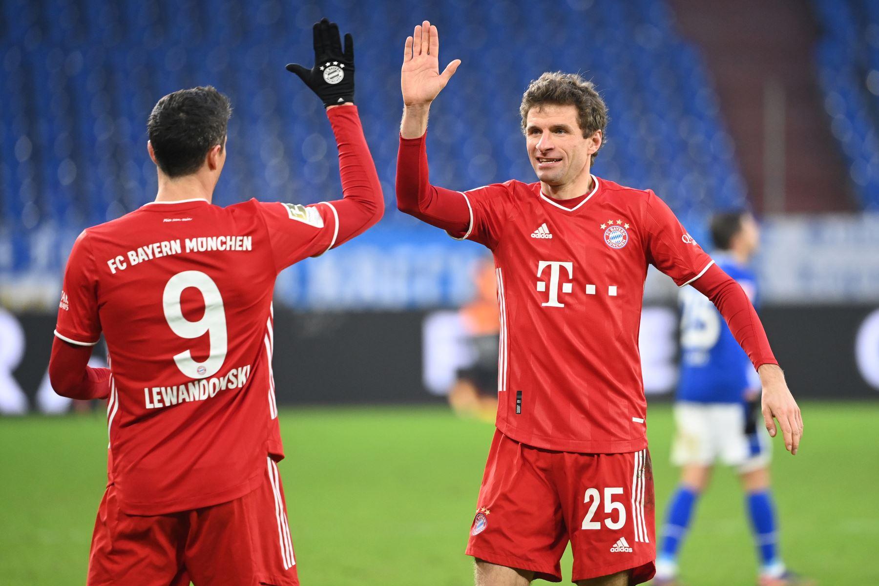 El delantero polaco del Bayern Múnich Robert Lewandowski celebra el gol del 0-2 con su compañero de equipo, el delantero alemán del Bayern Múnich Thomas Mueller durante el partido de fútbol de la Bundesliga de primera división alemana Schalke 04 v FC Bayern Múnich en Gelsenkirchen, Alemania occidental.  Foto.: AFP