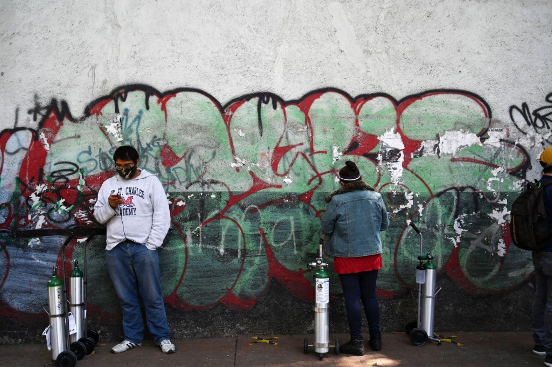 Las personas hacen fila con sus tanques de oxígeno para comprar en la Compañía Infra Medica en la Ciudad de México. Foto: AFP