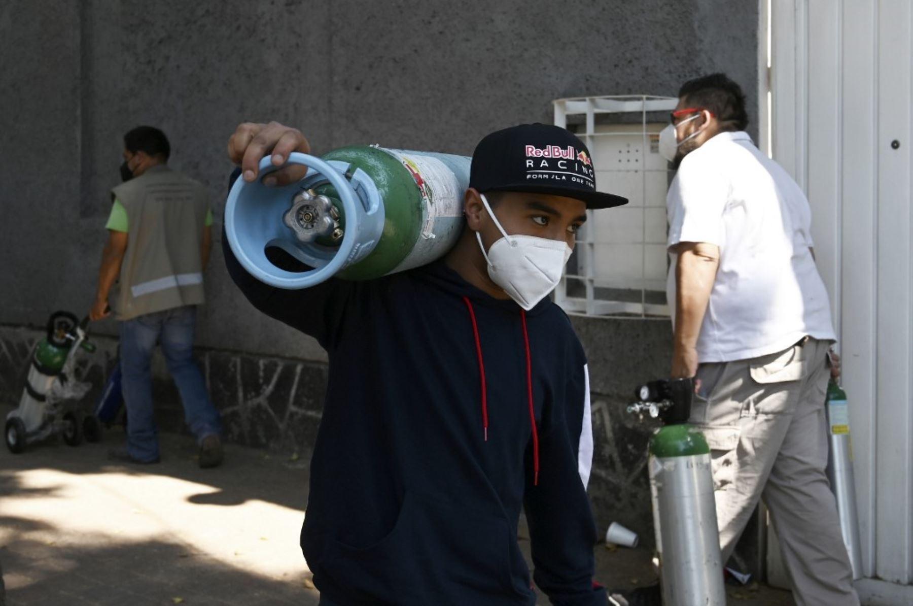 Un hombre lleva un tanque de oxígeno junto a una fila de personas que hacen cola para rellenar el suyo en la Compañía Infra Médica en la Ciudad de México. Foto: AFP