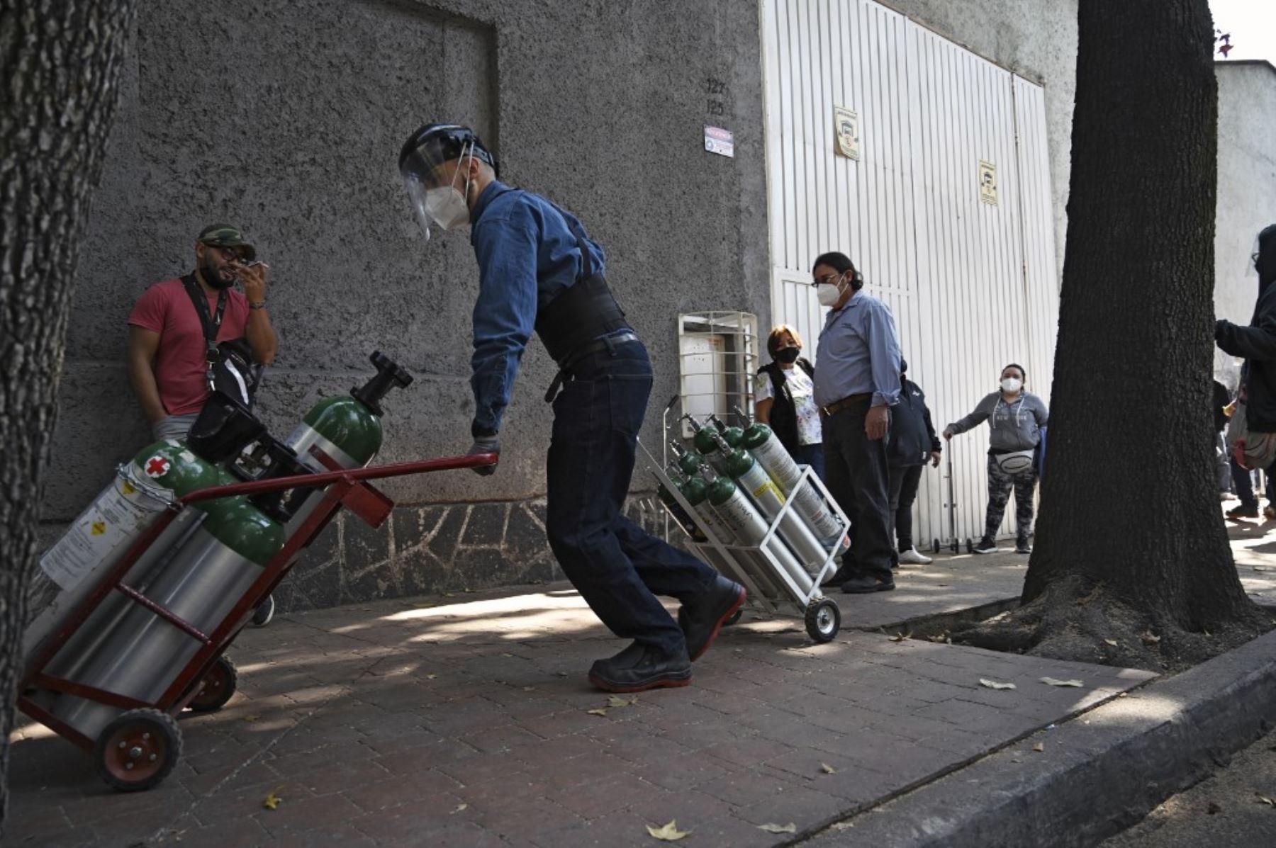 Personas hacen fila para rellenar los tanques de oxígeno en la Compañía Infra Medica en la Ciudad de México. Foto: AFP