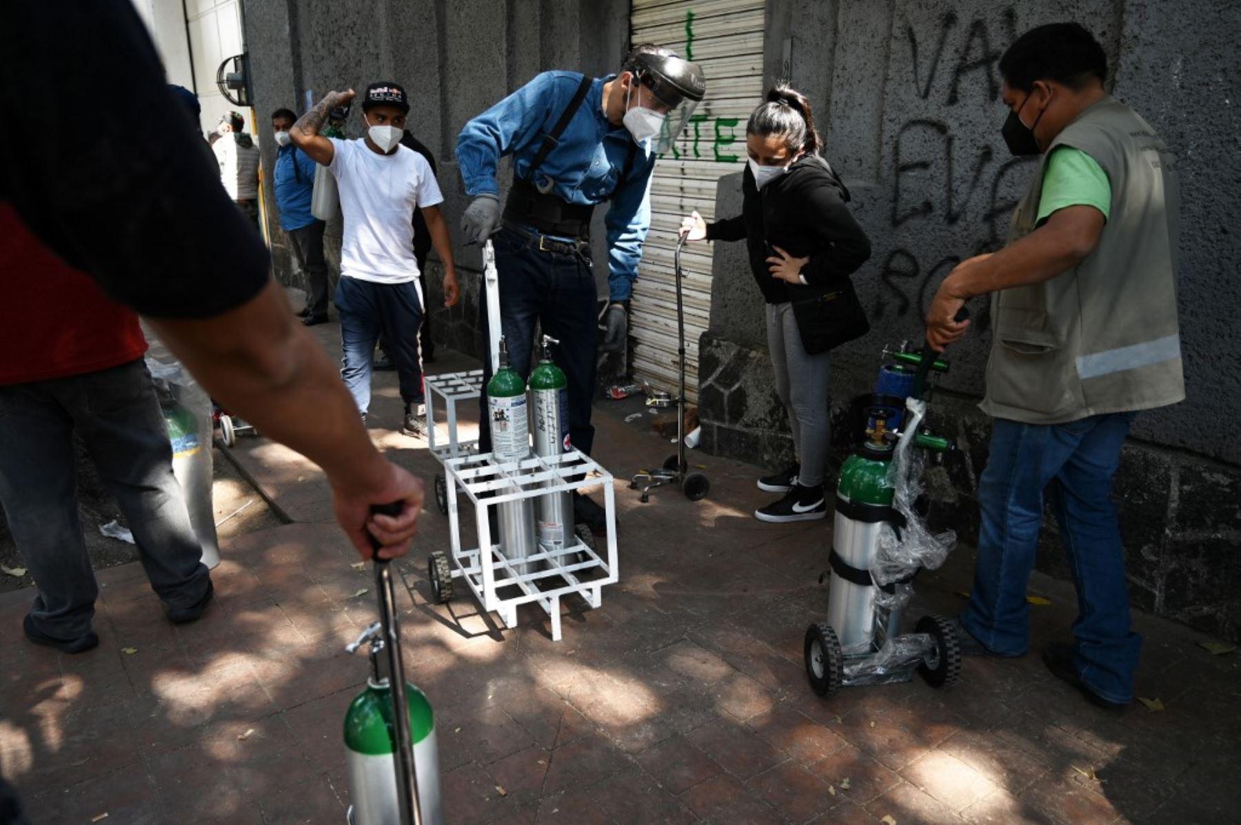 Un empleado de la Compañía Infra Medica entrega tanques de oxígeno rellenados a personas en una cola en la Ciudad de México. Foto: AFP