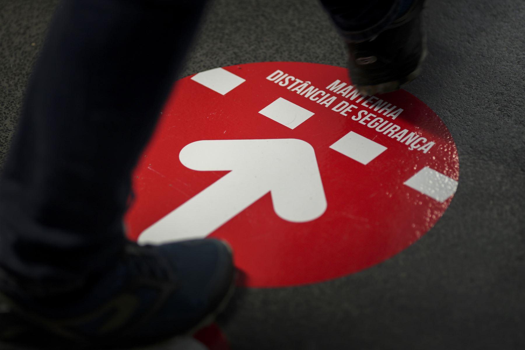 Un votante camina sobre un cartel de distanciamiento social durante las elecciones presidenciales portuguesas en un colegio electoral en el Parque das Nacoes en Lisboa, Portugal está votando a pesar del bloqueo pandémico del país. Foto: AFP