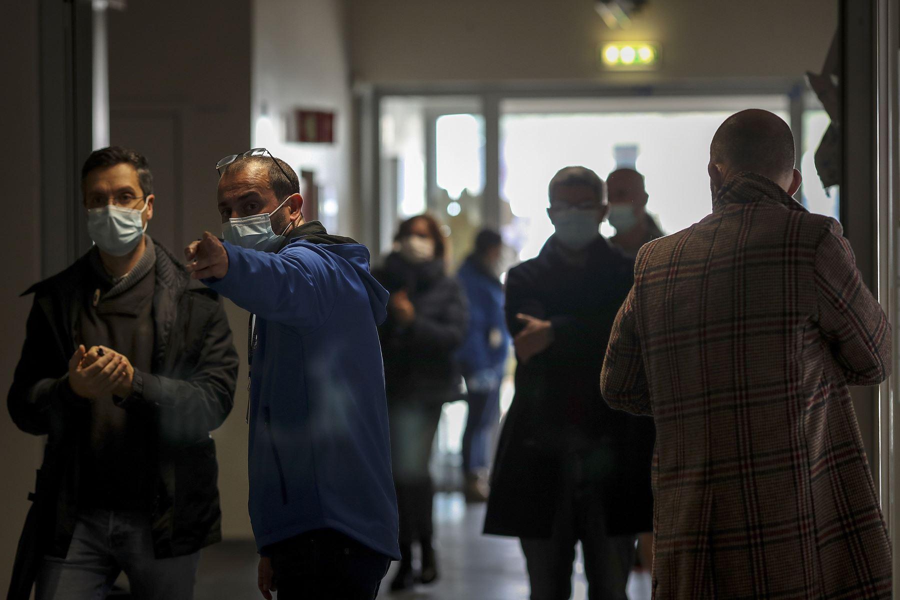 Un trabajador electoral con una máscara facial dirige a un votante a su centro de votación en las elecciones presidenciales portuguesas en una escuela en el Parque das Nações en Lisboa, Los portugueses votan hoy para las elecciones presidenciales.