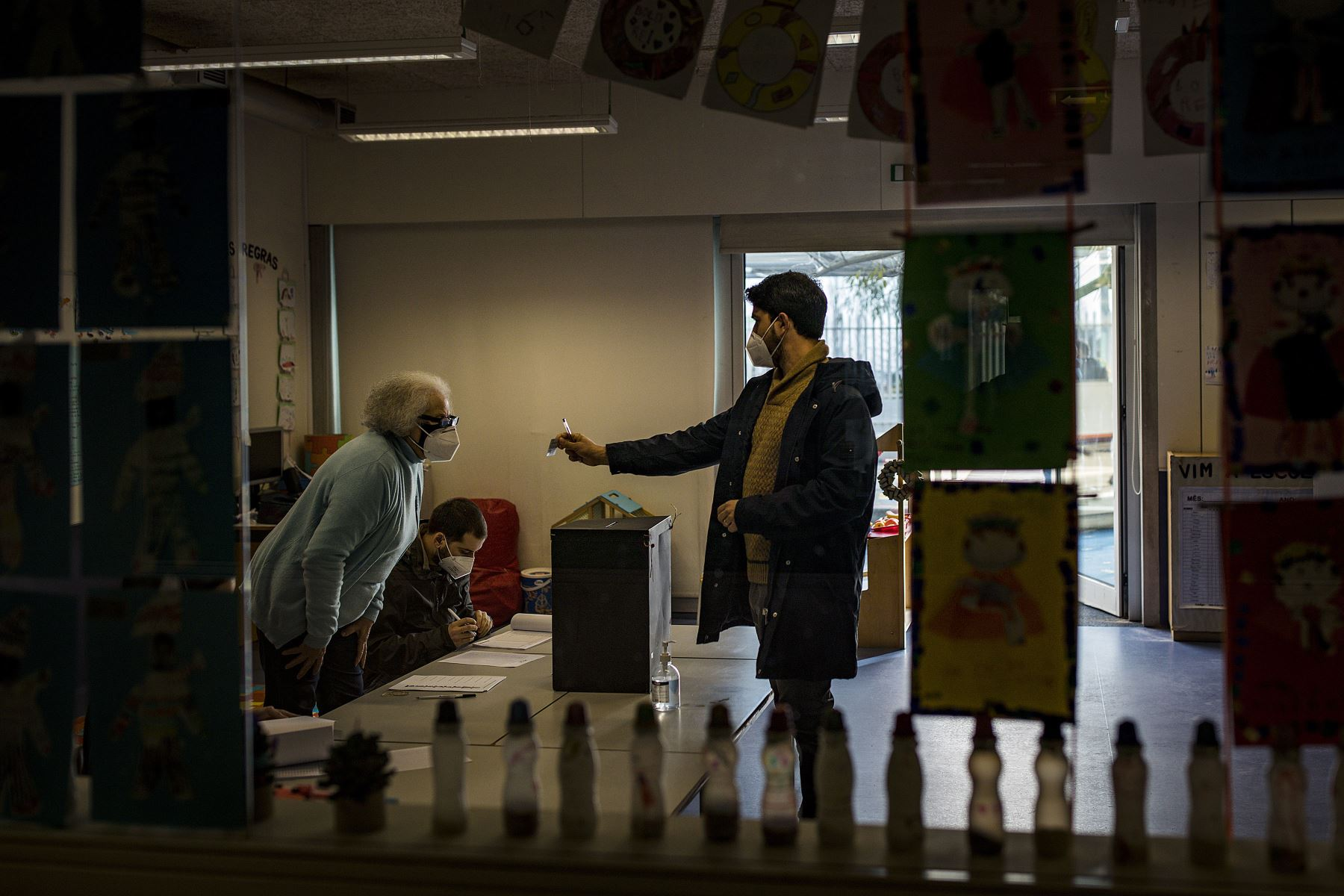 Un hombre muestra su tarjeta de identificación a los trabajadores electorales antes de votar para las elecciones presidenciales portuguesas en una escuela que se utiliza como centro de votación en el Parque das Nacoes en Lisboa, Portugal está votando a pesar del bloqueo pandémico del país.  Foto: AFP