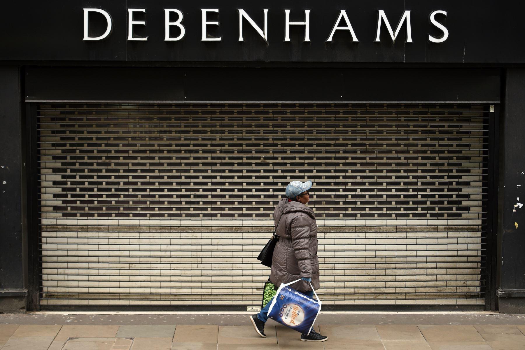 Una mujer pasa frente a las contraventanas en la entrada de los grandes almacenes Debenhams en Manchester, en el noroeste de Inglaterra. Foto: AFP