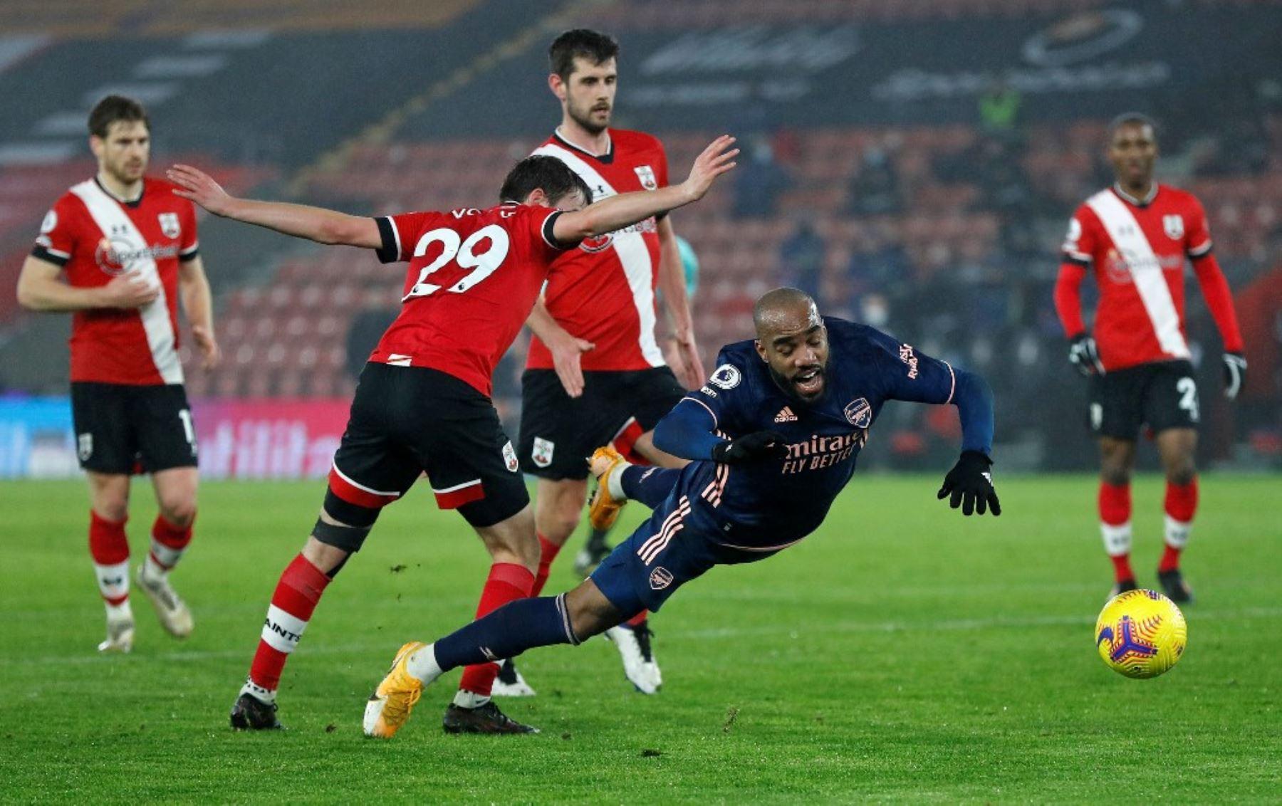 El defensa inglés de Southampton, Jake Vokins, compite con el delantero francés del Arsenal, Alexandre Lacazette, durante el partido de fútbol de la Premier League inglesa entre Southampton y Arsenal en el St Mary
