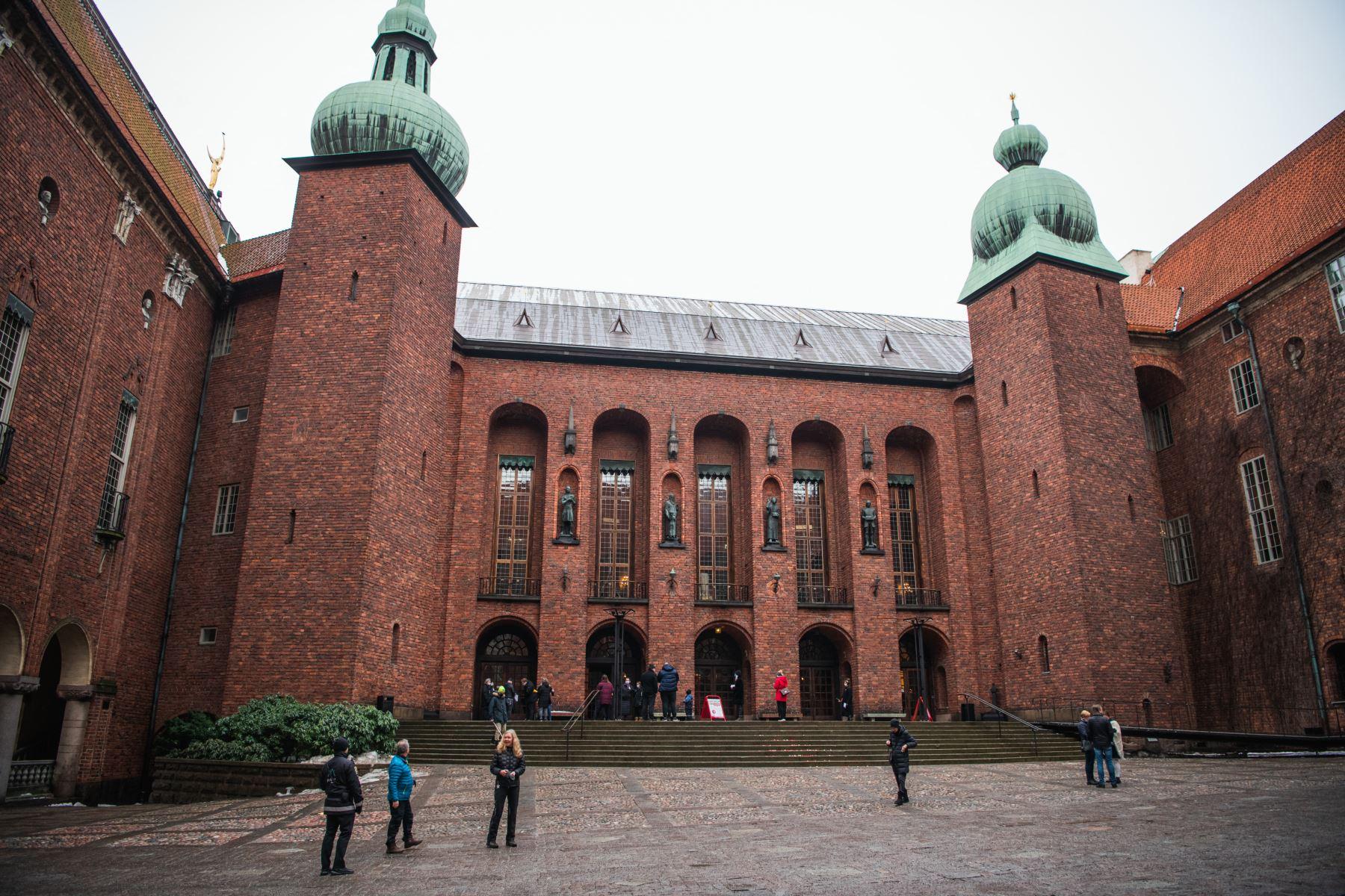 La gente espera su turno para entrar al Ayuntamiento de Estocolmo, conocido como sede de los banquetes del Premio Nobel y convertido ahora en un centro de vacunación covid-19. Foto: AFP