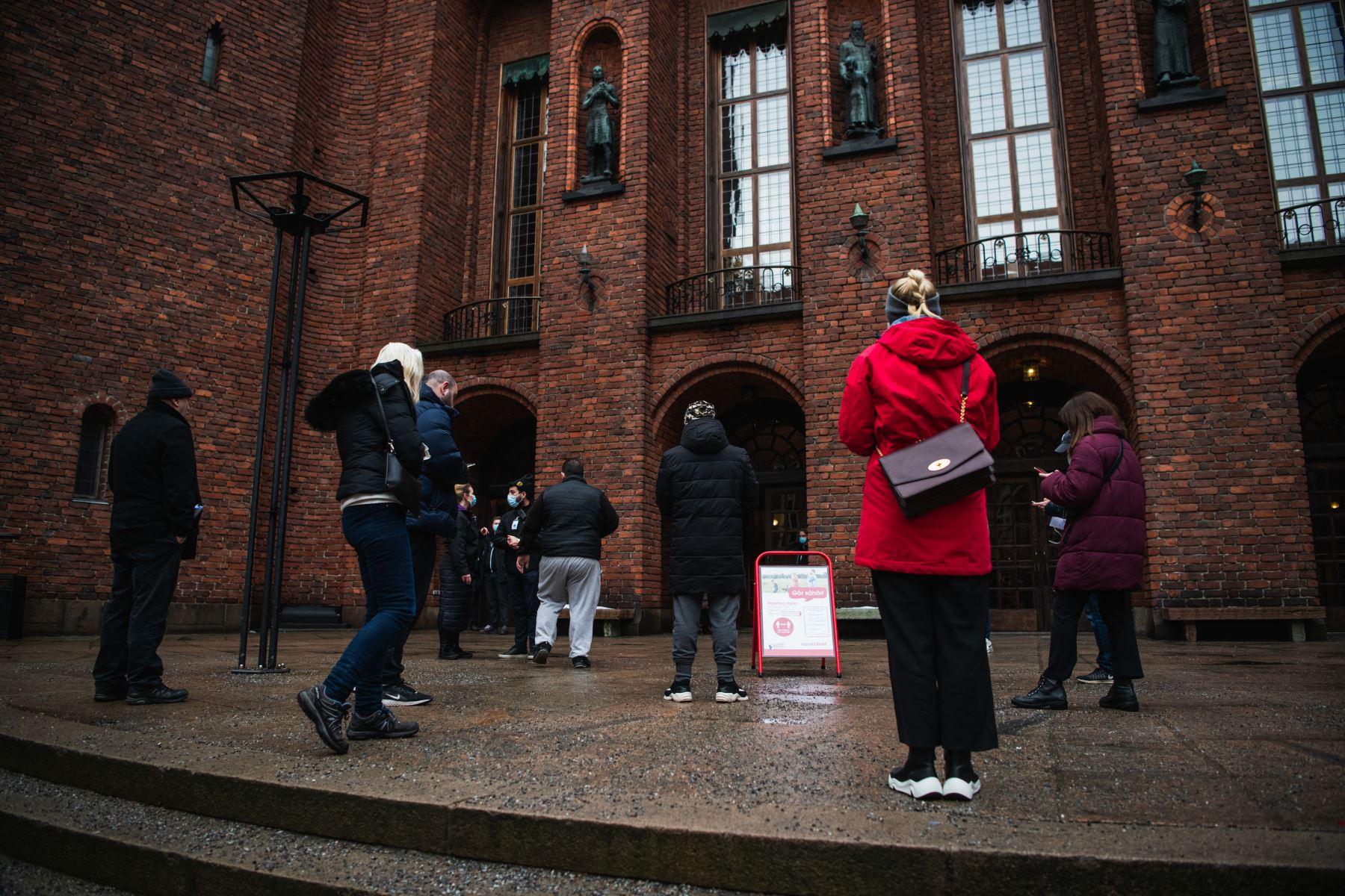 La gente espera su turno para entrar al Ayuntamiento de Estocolmo, conocido como sede de los banquetes del Premio Nobel y convertido ahora en un centro de vacunación covid-19  en la capital de Suecia, en medio del nuevo coronavirus. Foto: AFP