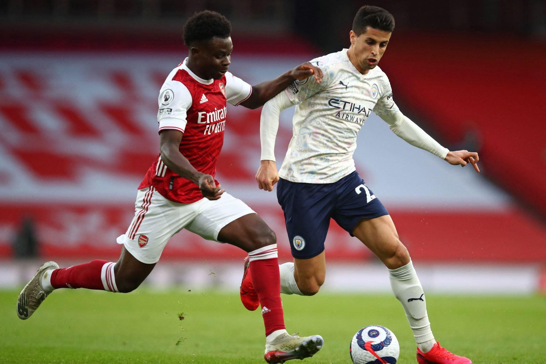 El delantero inglés del Arsenal Bukayo Saka compite con el defensor portugués del Manchester City Joao Cancelo durante el partido de fútbol de la Premier League inglesa entre el Arsenal y el Manchester City. Foto: AFP