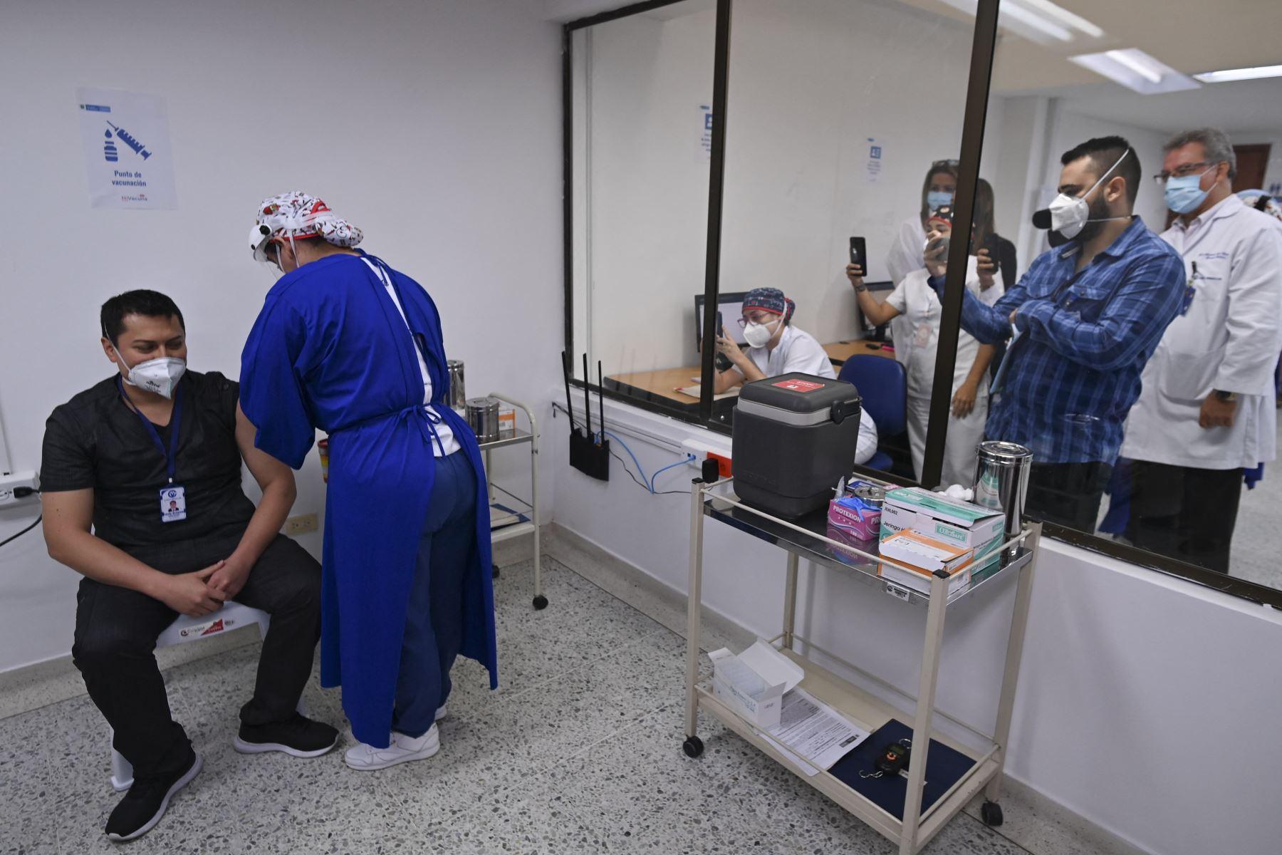 Trabajadores de salud toman fotografías de un médico siendo inoculado con la vacuna Pfizer-BioNTech contra COVID-19 en la Clínica Versalles, en Cali, Colombia. Desde el comienzo de la epidemia más de 111.331.990 personas contrajeron la enfermedad. De ellas al menos 68.323.000 se recuperaron, según las autoridades. Foto: AFP