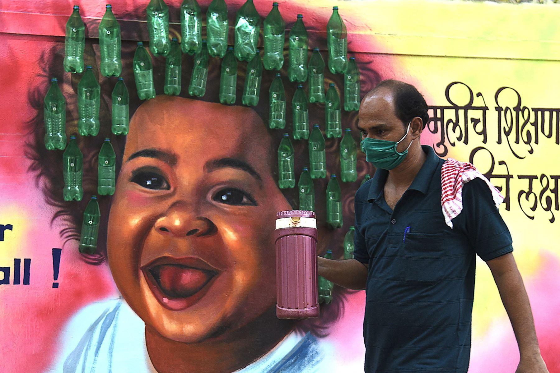 Un hombre con una mascarilla pasa junto a un mural después de que las autoridades impusieran nuevas restricciones como medida preventiva contra la propagación del coronavirus Covid-19, en Mumbai. Desde el comienzo de la epidemia más de 111.331.990 personas contrajeron la enfermedad. De ellas al menos 68.323.000 se recuperaron, según las autoridades. Foto: AFP