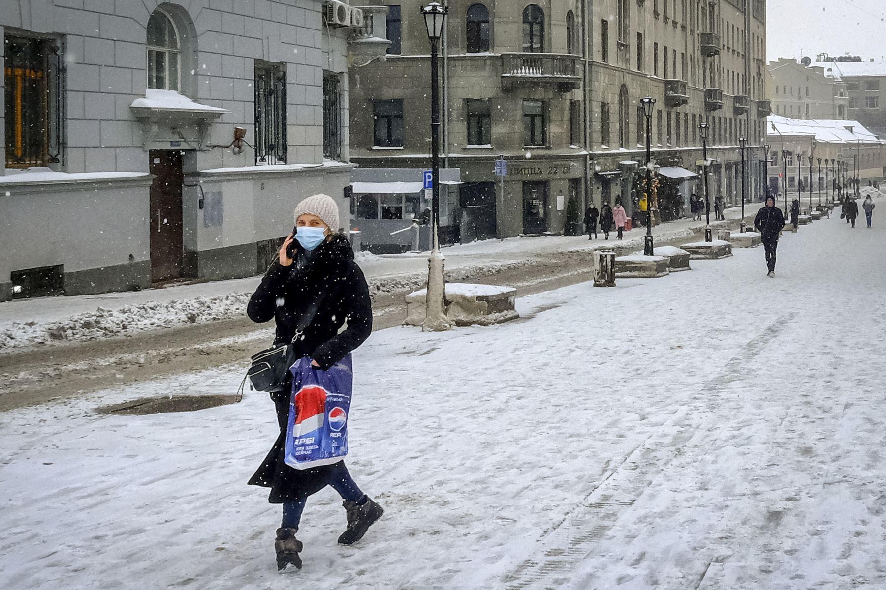 Una mujer con una mascarilla protectora contra la pandemia Covid-19, camina en la nieve por una calle en el centro de Moscú. Desde el comienzo de la epidemia más de 111.331.990 personas contrajeron la enfermedad. De ellas al menos 68.323.000 se recuperaron, según las autoridades. Foto: AFP