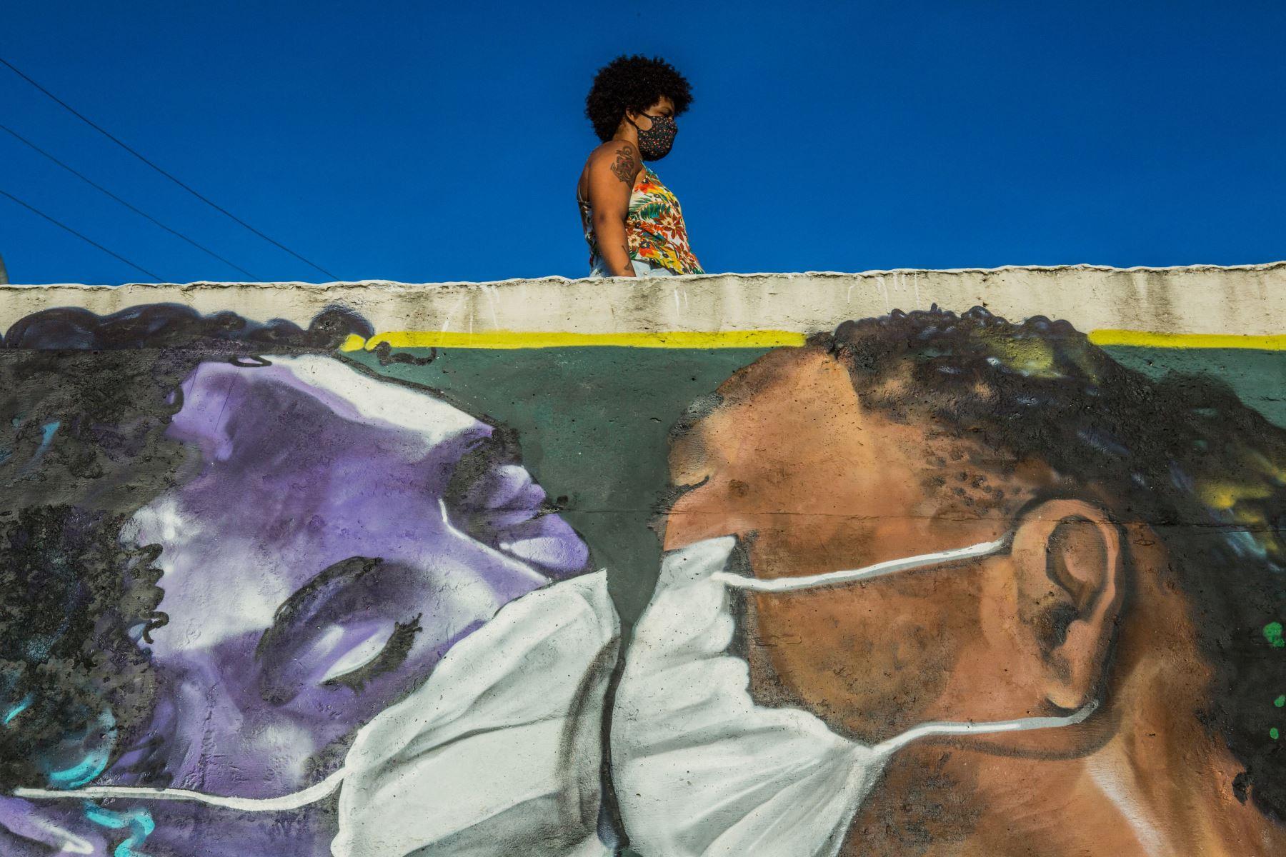 Una mujer con una máscara facial se encuentra sobre un graffiti del artista Marcos Costa, o Spray Cabuloso, en la entrada de la favela Solar de Unhao en Salvador, estado de Bahía, Brasil. Desde el comienzo de la epidemia más de 111.331.990 personas contrajeron la enfermedad. De ellas al menos 68.323.000 se recuperaron, según las autoridades. Foto: AFP