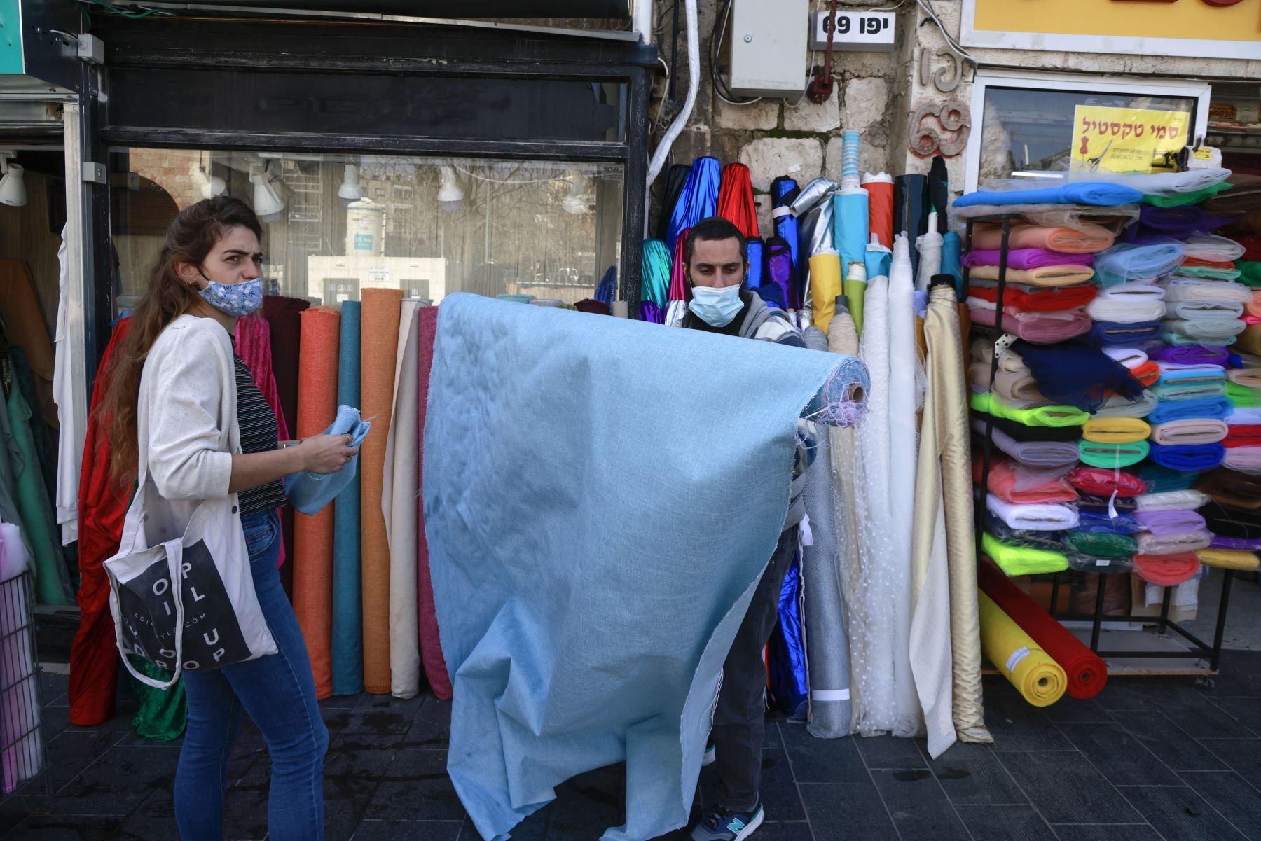 Una mujer compra telas en una tienda abierta en Jerusalén, el 7 de febrero de 2021, después de que las autoridades israelíes anunciaran un alivio gradual de las restricciones por el coronavirus. Foto: AFP