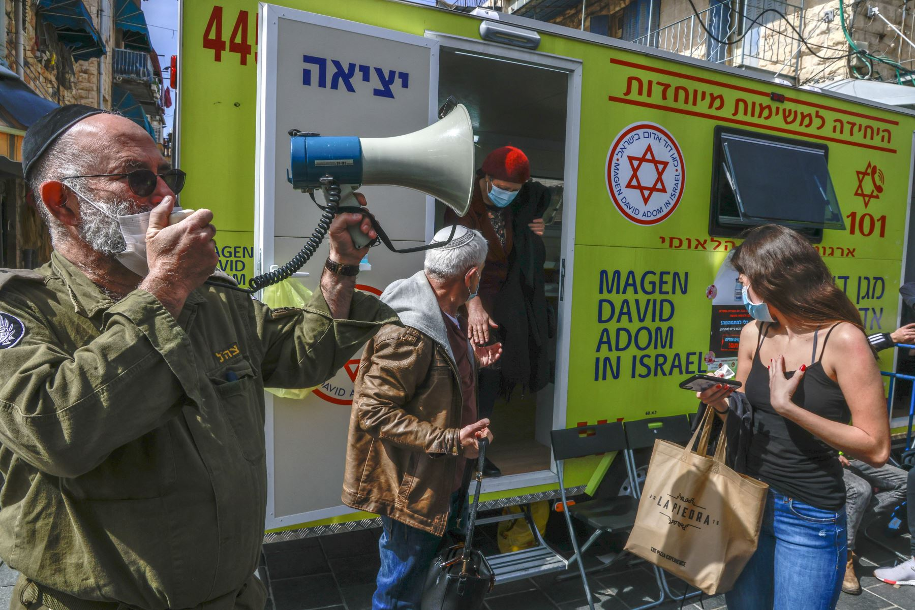 Un oficial del Home Front Command de Israel usa un megáfono para llamar a los pacientes durante una campaña de vacunación contra el coronavirus en el mercado Mahane Yehuda en Jerusalén el 22 de febrero de 2021. Foto: AFP