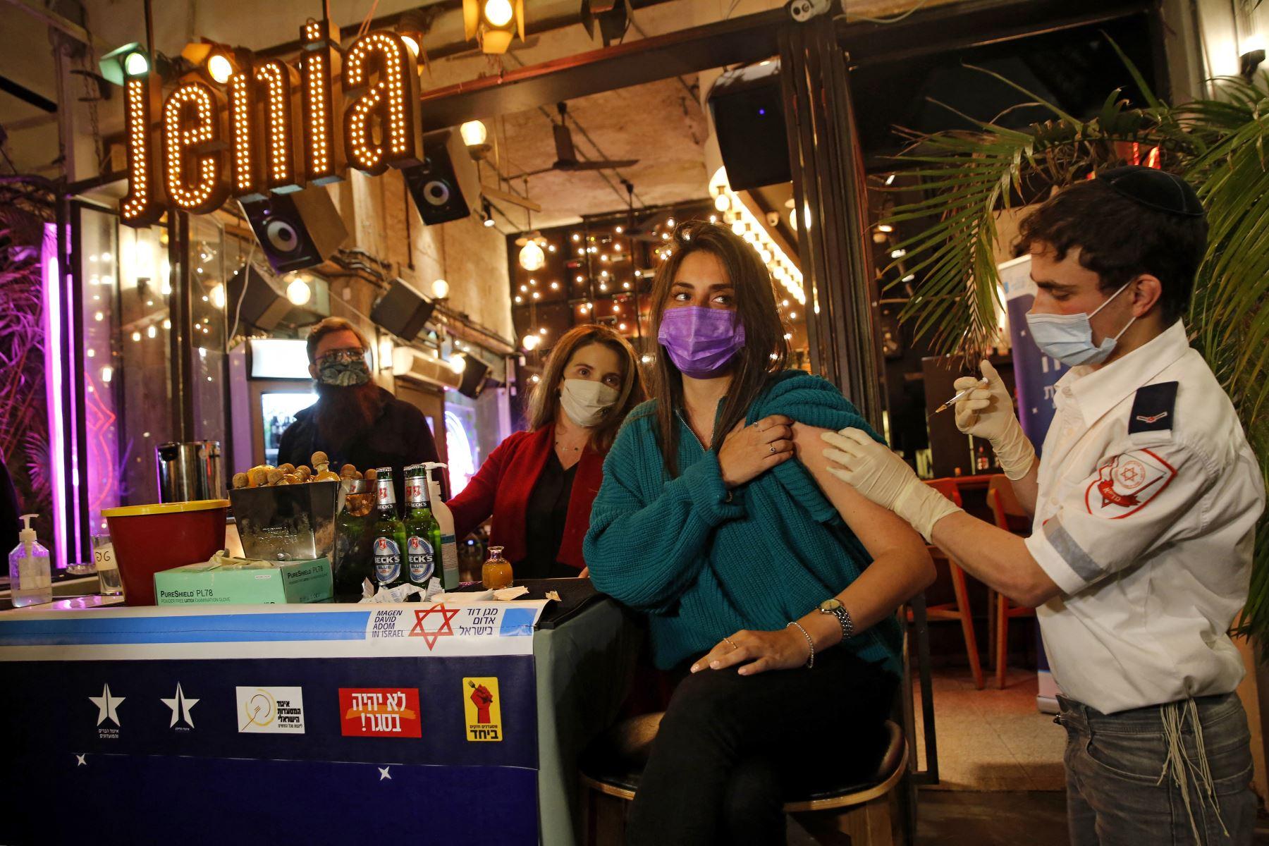 Un trabajador de salud administra la vacuna COVID-19 a un israelí en un bar en la ciudad costera de Tel Aviv, en Israel. Foto: AFP