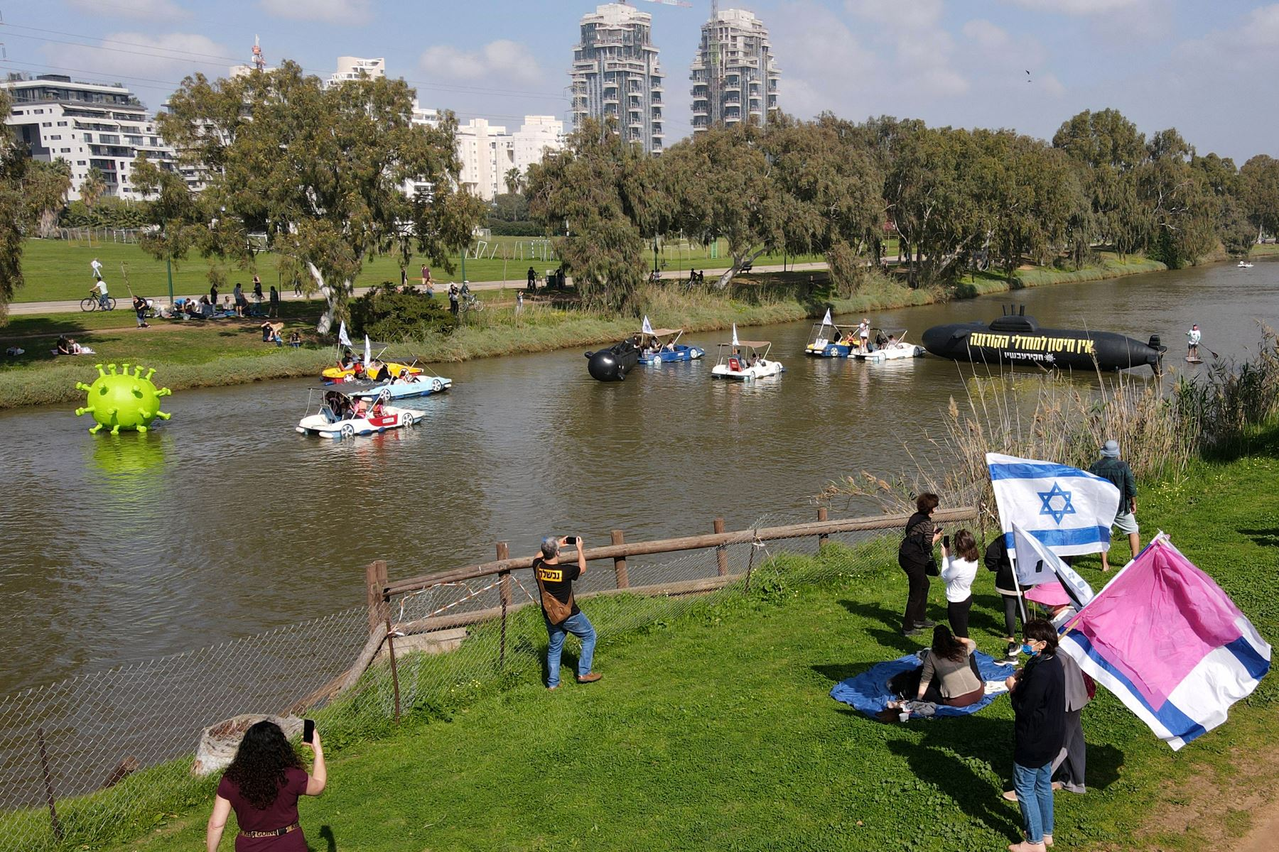 Objetos inflables una representación del coronavirus por el río Yarkon, mientras los israelíes protestan en medio de la crisis por la pandemia. Foto: AFP