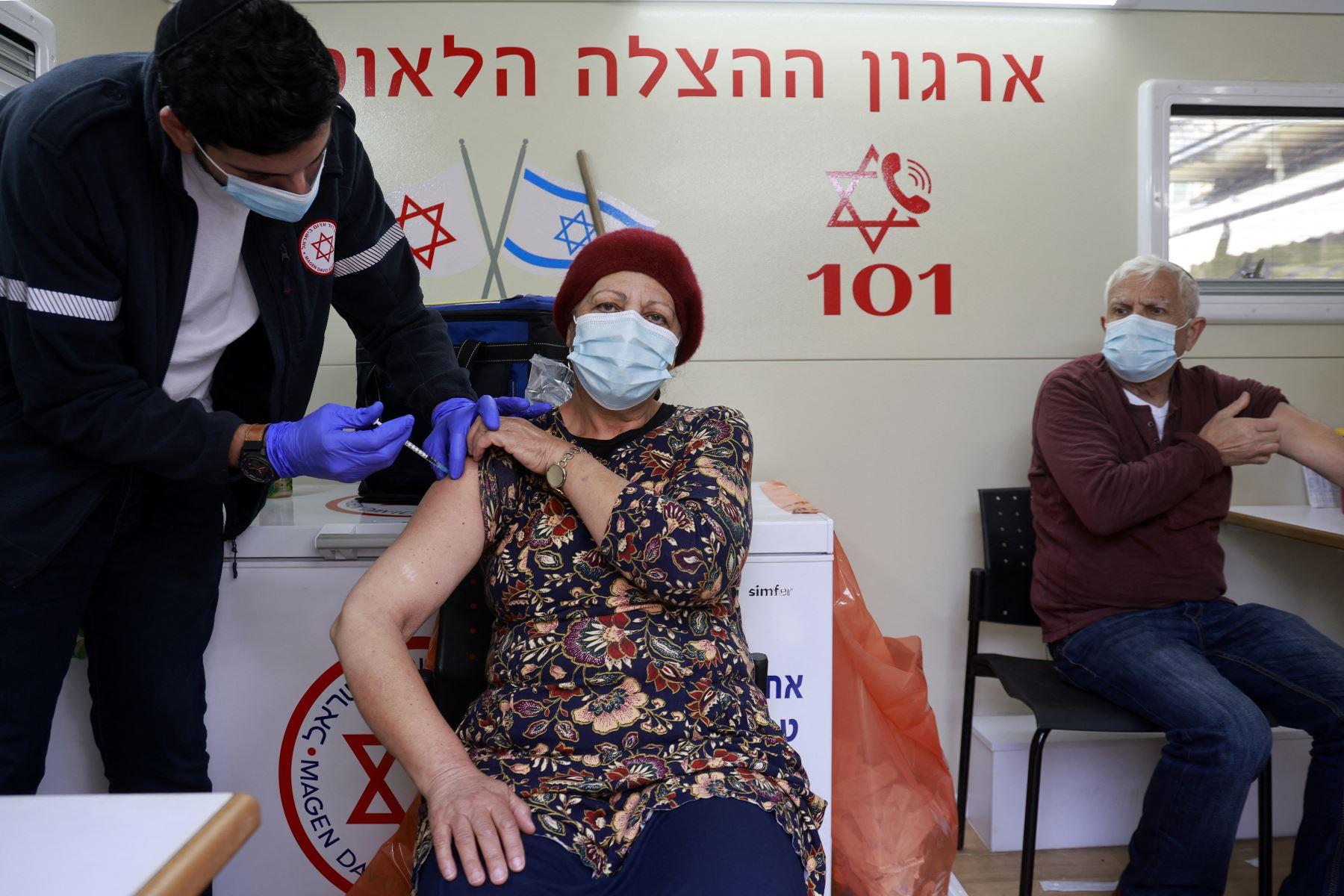 Un paramédico administra una dosis de la vacuna contra el coronavirus de Pfizer BioNTech a una mujer dentro de una clínica móvil de Magen David Adom en el mercado Mahane Yehuda en Jerusalén, el 22 de febrero de 2021. Foto: AFP