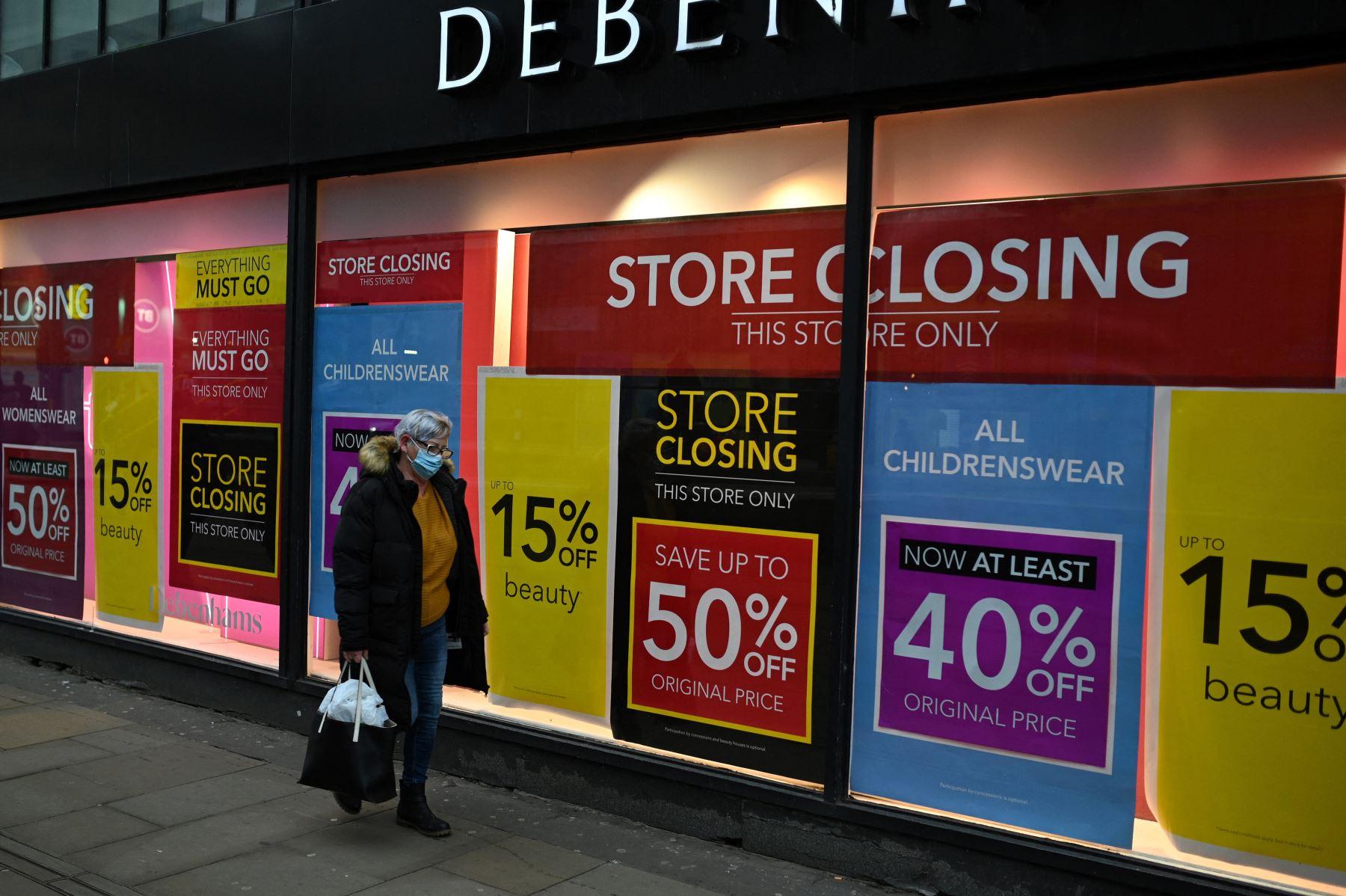 Un peatón pasa junto a los carteles de rebajas en las ventanas de Debenhams en el centro de la ciudad de Manchester el 19 de febrero de 2021, mientras la vida continúa bajo el tercer bloqueo británico. Foto: AFP