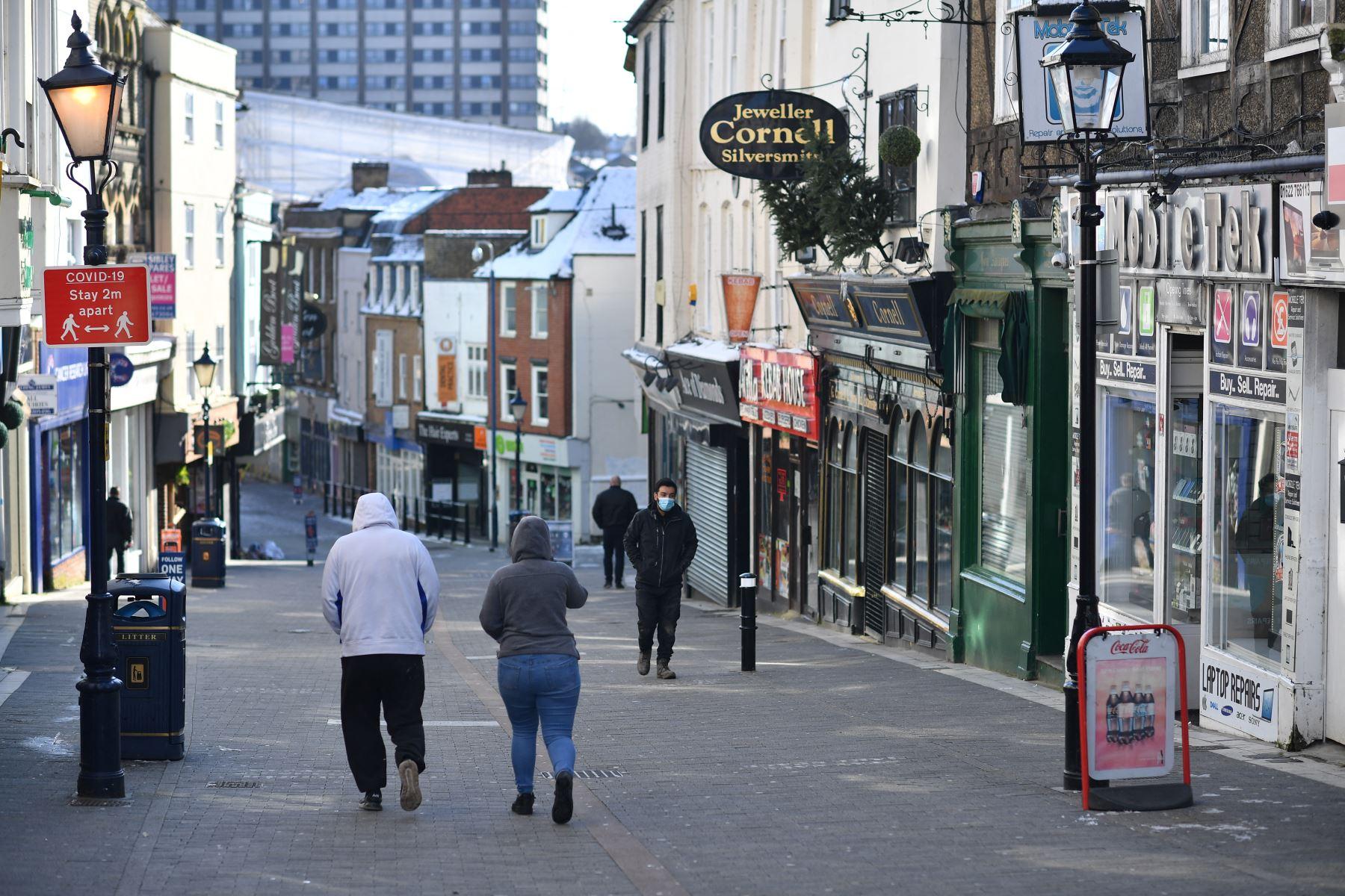 Los peatones caminan por una calle principal con las tiendas cerradas en Maidstone, sureste de Inglaterra, el 12 de febrero de 2021 mientras la vida continúa en el tercer cierre de coronavirus. Foto: AFP