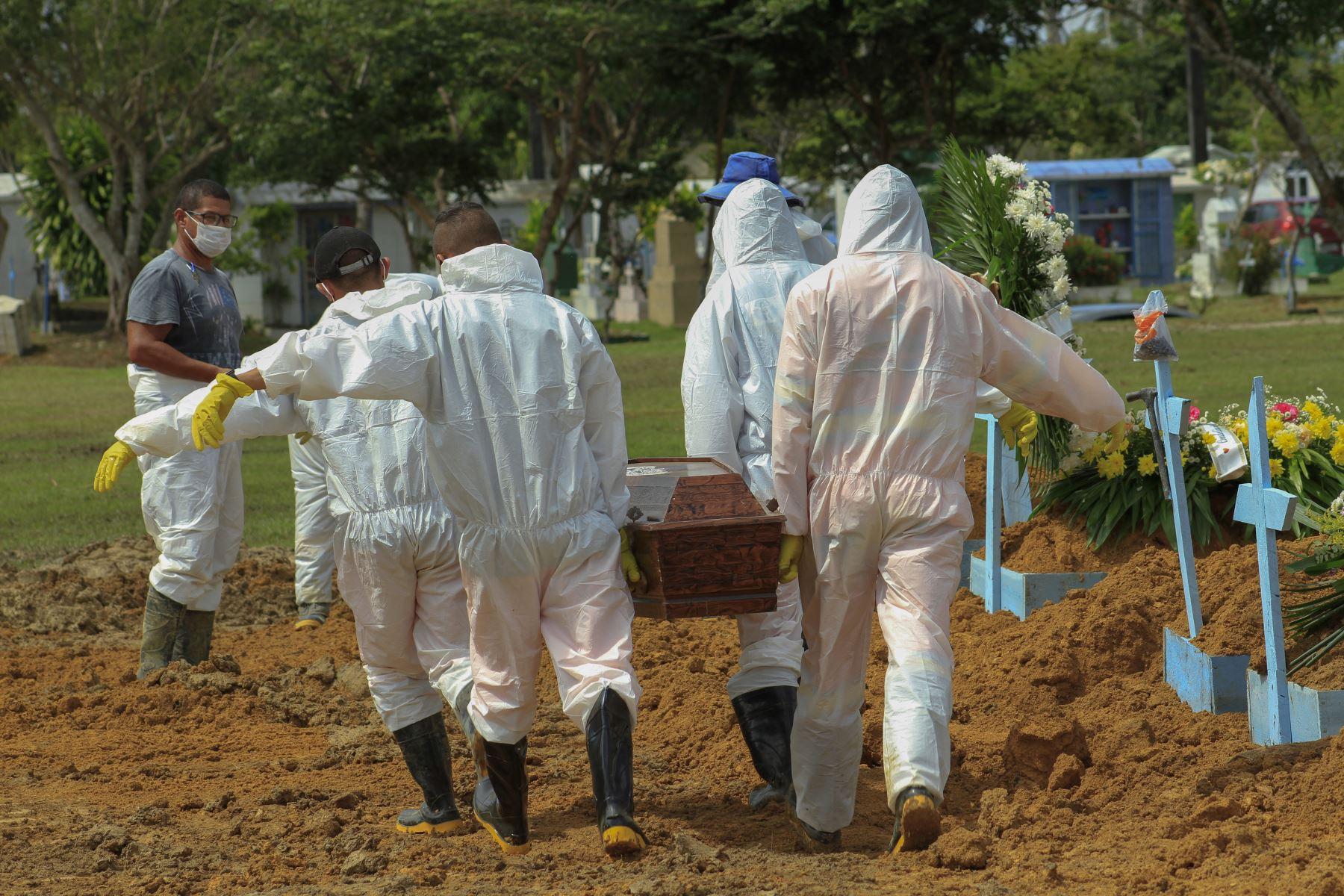 Sepultureros cargan el ataúd de una víctima del COVID-19 en el cementerio de Nossa Senhora Aparecida en Manaus, estado de Amazonas, Brasil, el 22 enero de 2021. Foto: AFP